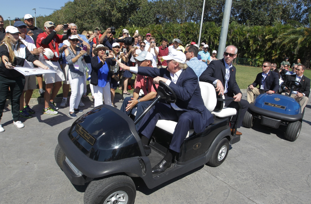 Republican presidential candidate Donald Trump greets supporters as he drives himself around the golf course to watch the final round of the Cadillac Championship golf tournament, Sunday, March 6, 2016, in Doral, Fla. (AP Photo/Luis Alvarez)
