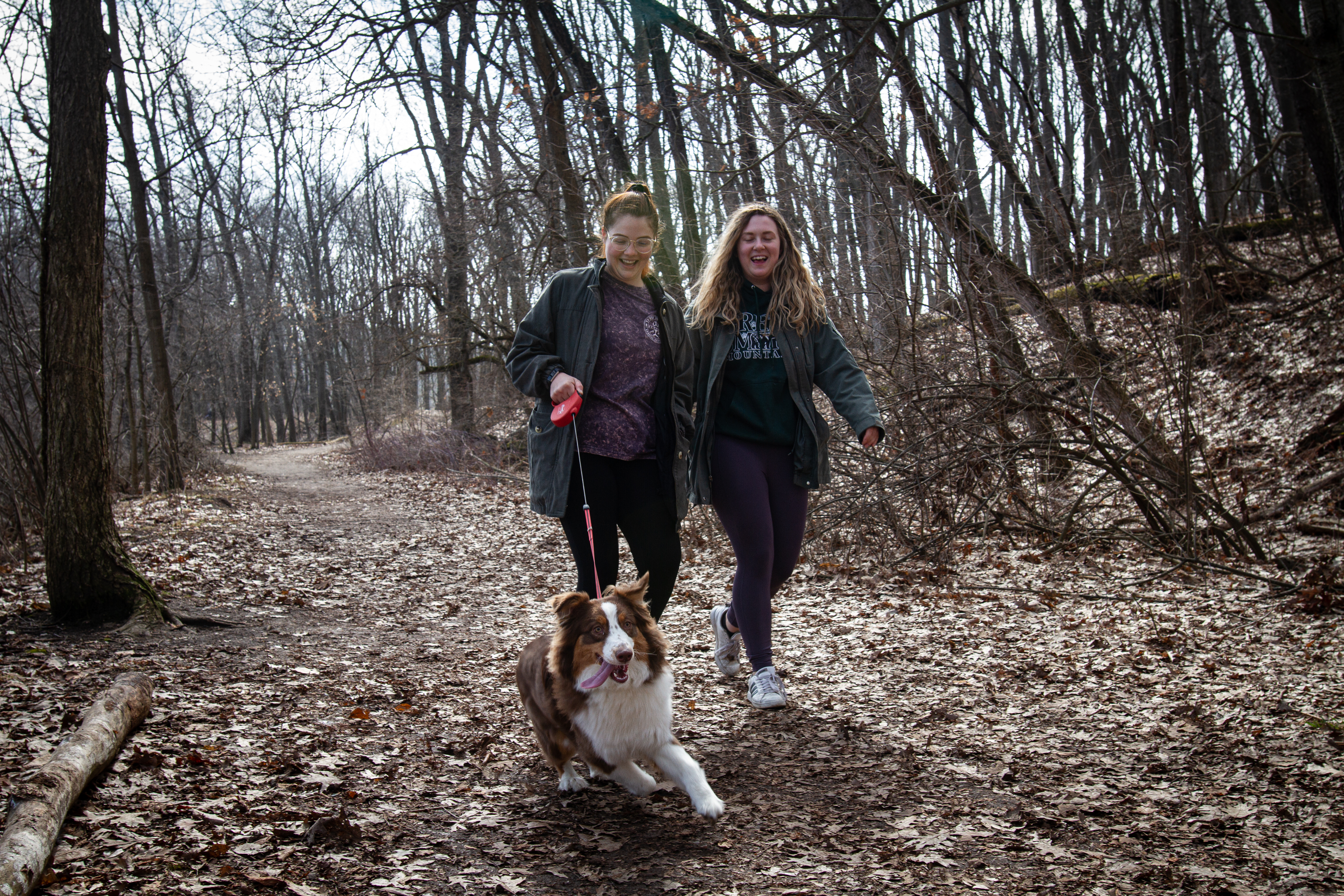Mariah Stefani (left) and Lorin Miley (right) take Annie the dog for a walk at Asylum Lake Preserve on Wednesday, March 25.{ }(WWMT/Sarah White)