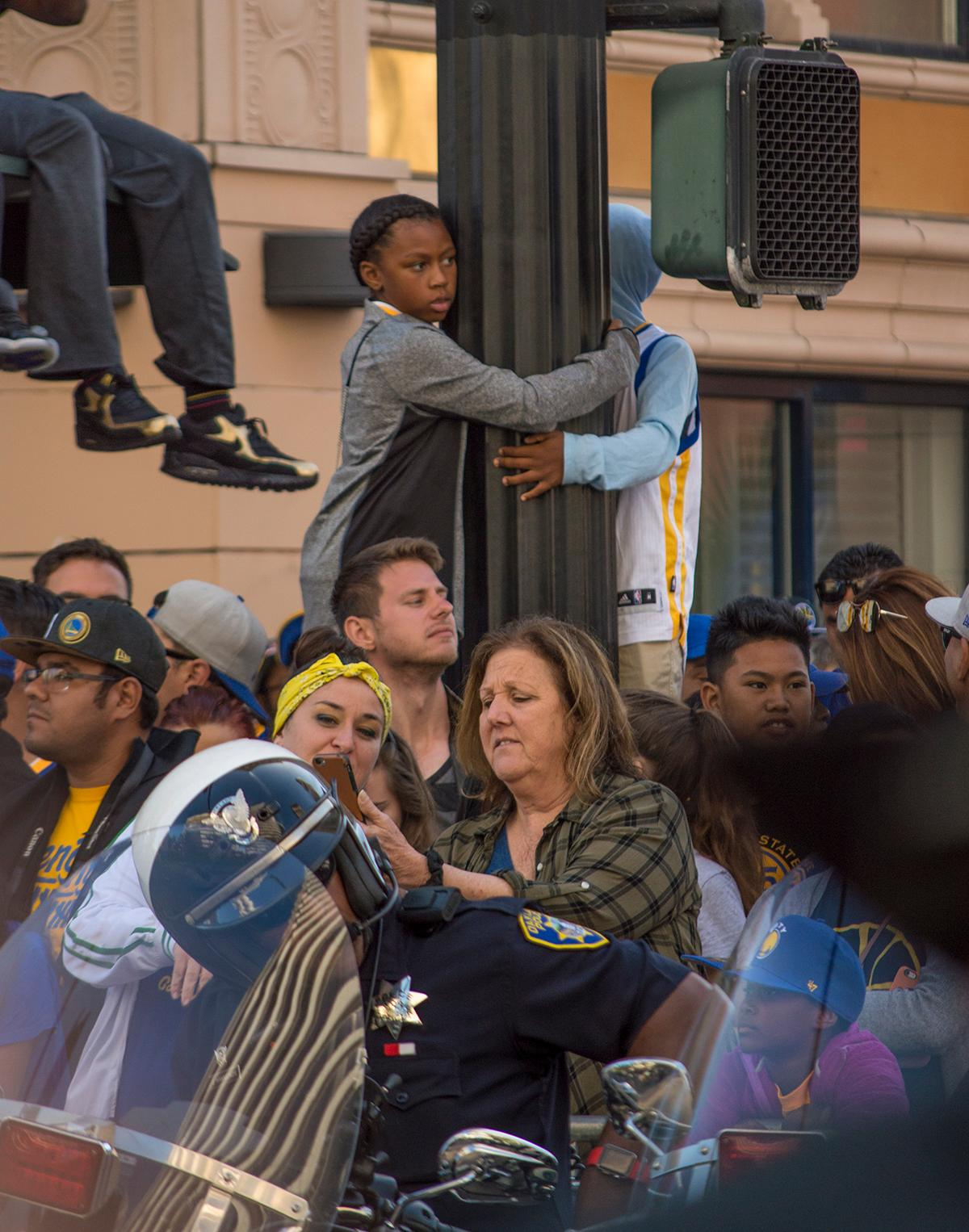 Young fans on 13th Street in Oakland, California climb up to higher ground to get a better view of the Golden State Warriors victory parade. Photo by Emily Gonzalez, Oregon News Lab.