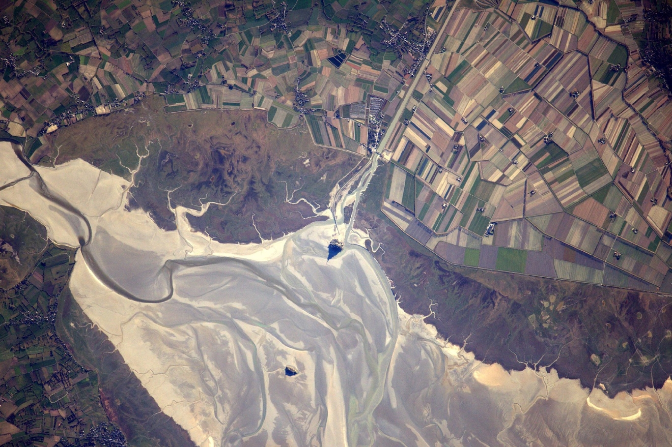 The Mont-Saint-Michel is famous for only being accessible at low tide. We were lucky to fly over at the right time to capture the beauty of its shadow, sketching its silhouette in the sand.  (Photo & Caption: Thomas Pesquet // NASA)
