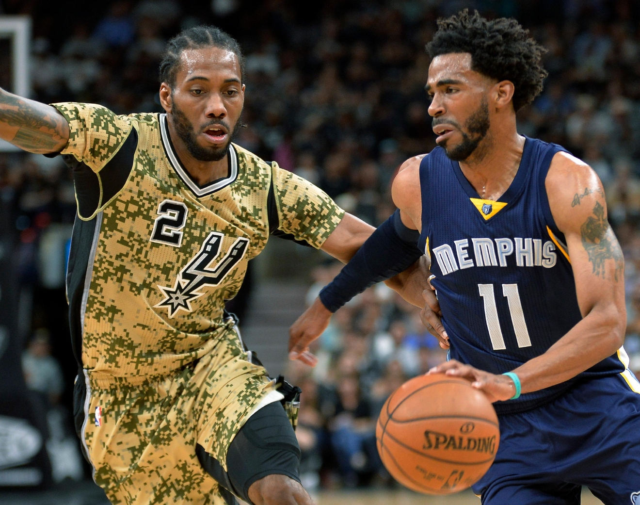 Memphis Grizzlies guard Mike Conley (11) drives around San Antonio Spurs forward Kawhi Leonard during the first half of an NBA basketball game, Thursday, March 23, 2017, in San Antonio. (AP Photo/Darren Abate)p