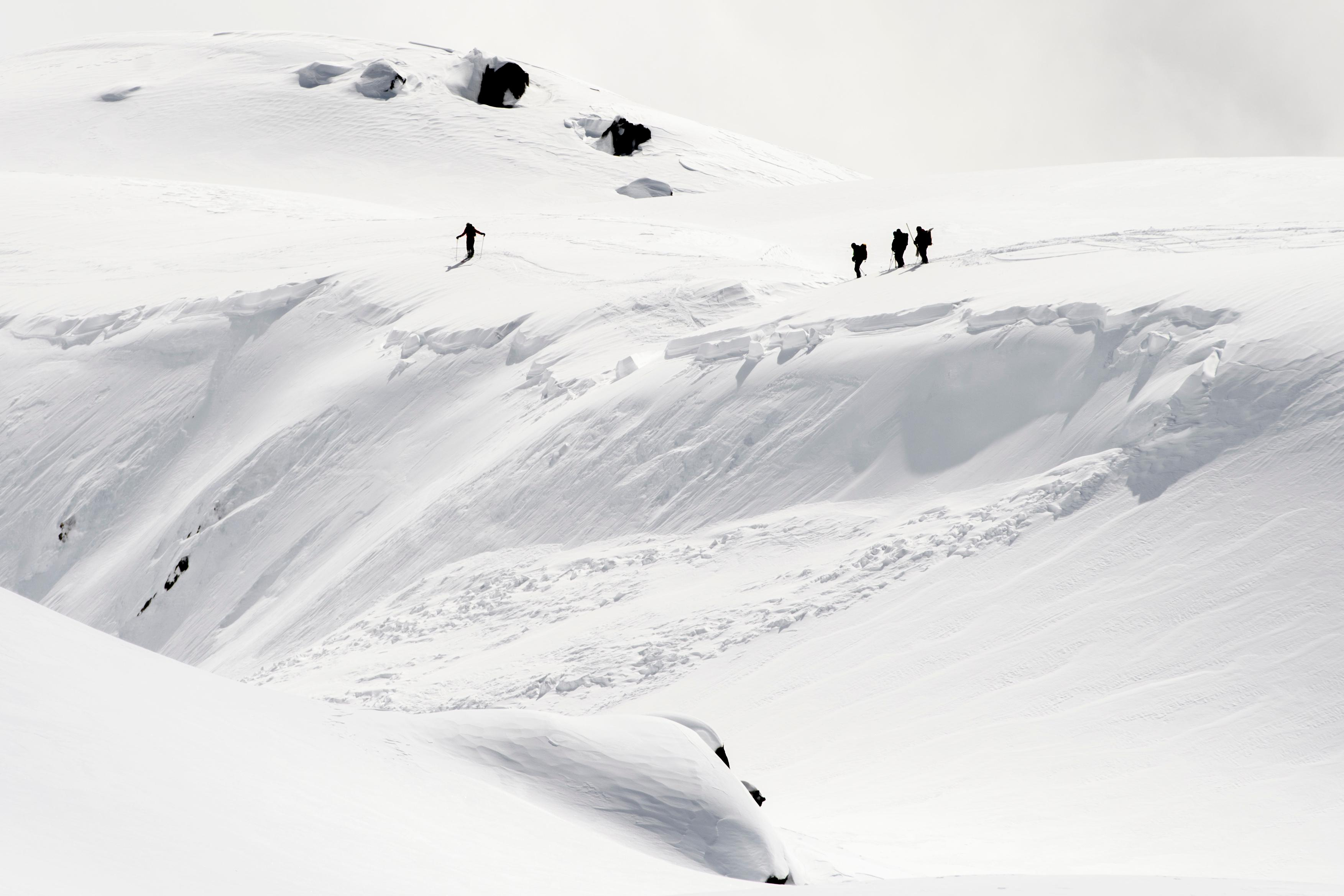 Rescue crews walk at an avalanche site near Fiesch, Switzerland, Sunday, April 1, 2018. Swiss police say three people have been killed in an avalanche in the Alps. Another two were taken to a hospital with light injuries. Police  say the avalanche hit the group of five skiers on Saturday afternoon. The group had set off from an Alpine hut earlier in the day to cross the Aletsch glacier in southern Switzerland. (Jean-Christophe Bott/Keystone via AP)