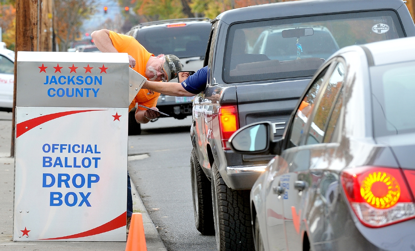 Voters drop off ballots by foot and by vehicle at a box outside election headquarters in Medford, Ore., Monday, Nov. 7, 2016. (Denise Baratta/The Medford Mail Tribune via AP)