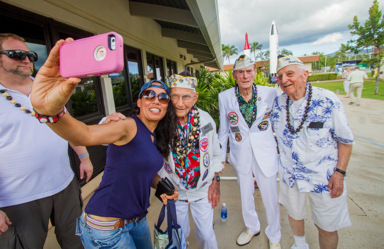 "In this Monday, Dec. 5, 2016 photo, about 30 Pearl Harbor Survivors with the ""Greatest Generation"" vets meet and greet with visitors at the Pearl Harbor Visitor Center in Honolulu. At left, Bianca Coronado takes a selfie with Pearl Harbor survivors from left, Stuart ""Stu"" Hedley, Jack Holder and Ed Stone. On Wednesday, Dec. 7, thousands of servicemen and women and members of the public are expected to attend the 75th anniversary ceremony of the attack on Pearl Harbor that left more than 2,300 service people dead. (Dennis Oda/The Star-Advertiser via AP)"