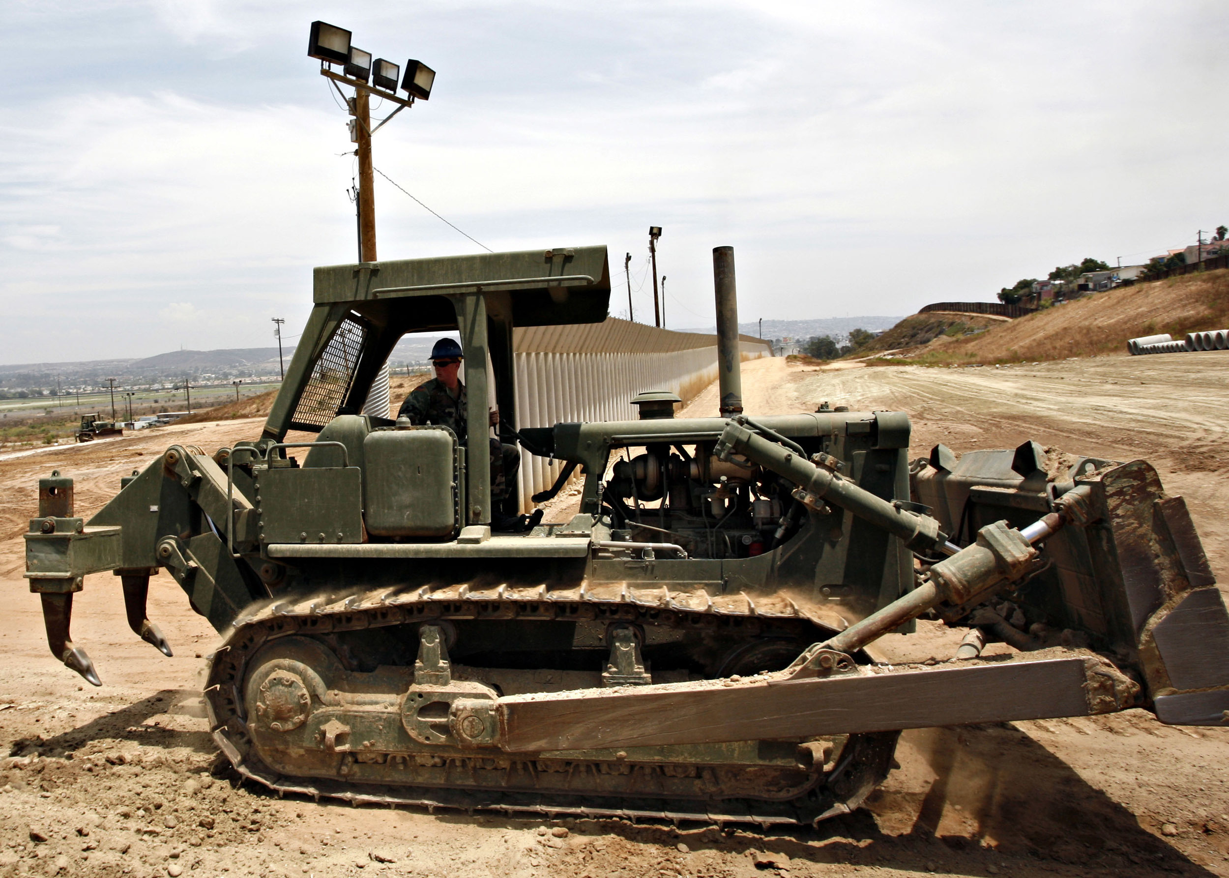 FILE - In this July 19, 2006, file photo, a California Army National Guardsman grades dirt with a tractor next to the second U.S.-Mexico border fence in San Diego. President Donald Trump said April 3, 2018, he wants to use the military to secure the U.S.-Mexico border until his promised border wall is built. The Department of Homeland Security and White House did not immediately respond to requests for comment. At the Pentagon, officials were struggling to answer questions about the plan, including rudimentary details on whether it would involve National Guard members, as similar programs in the past have done. But officials appeared to be considering a model similar to a 2006 operation in which former President George W. Bush deployed National Guard troops to the southern border in an effort to increase security and surveillance.(AP Photo/Denis Poroy, File)