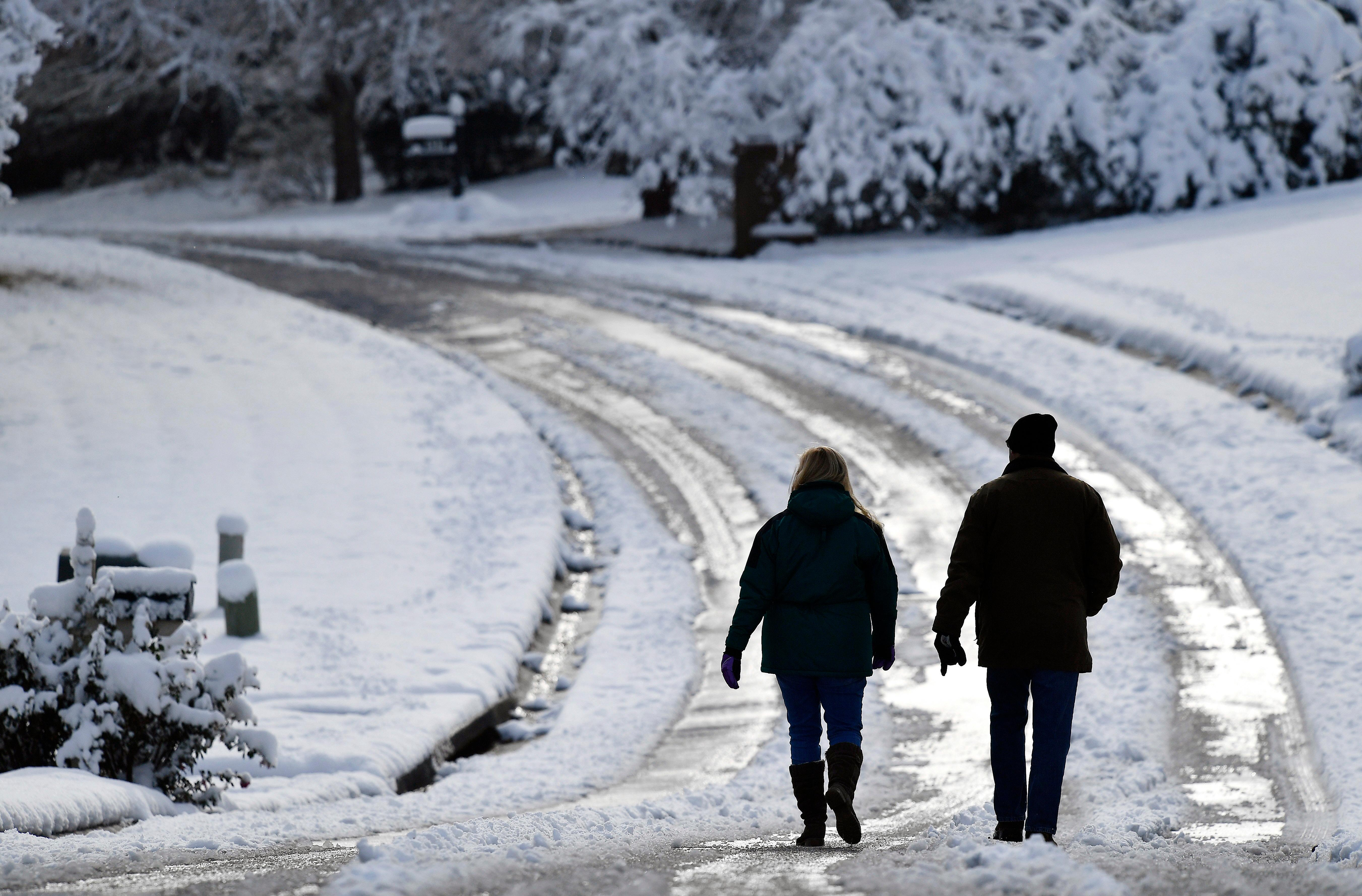 People walk down a snow covered road after a heavy snow, Saturday, Dec. 9, 2017, in Kennesaw, Ga. The frigid temperatures behind a cold front combined with moisture off the Gulf of Mexico to bring unusual wintry weather to parts of the South. (AP Photo/Mike Stewart)