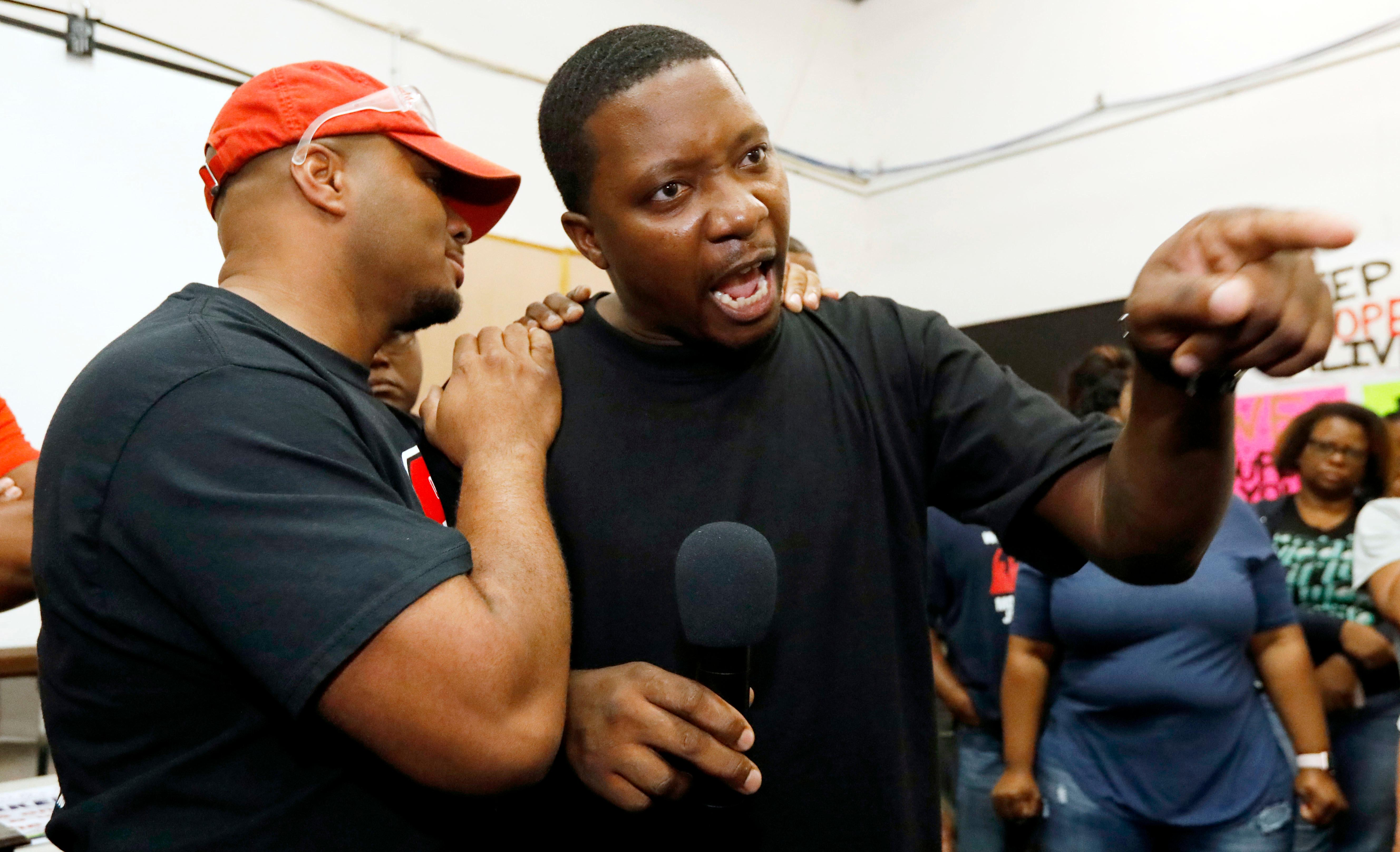 Nissan employee Morris Mock, left, consoles colleague Antonio Hoover as he expresses his disappointment at losing their bid to form a union at the Nissan vehicle assembly plant in Canton, Miss., Friday, Aug. 4, 2017.  (AP Photo/Rogelio V. Solis)
