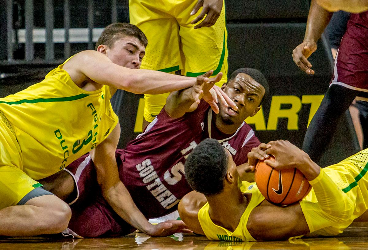 The Duck's Payton Pritchard (#3) and Kenny Wooten (#1) fight for the ball on the floor with the Tiger's Trayvon Reed (#5). The Oregon Ducks defeated Texas Southern Tigers 74-68. The Ducks are now 7-3 overall in the Pac-12. Photo by August Frank. Oregon News Lab
