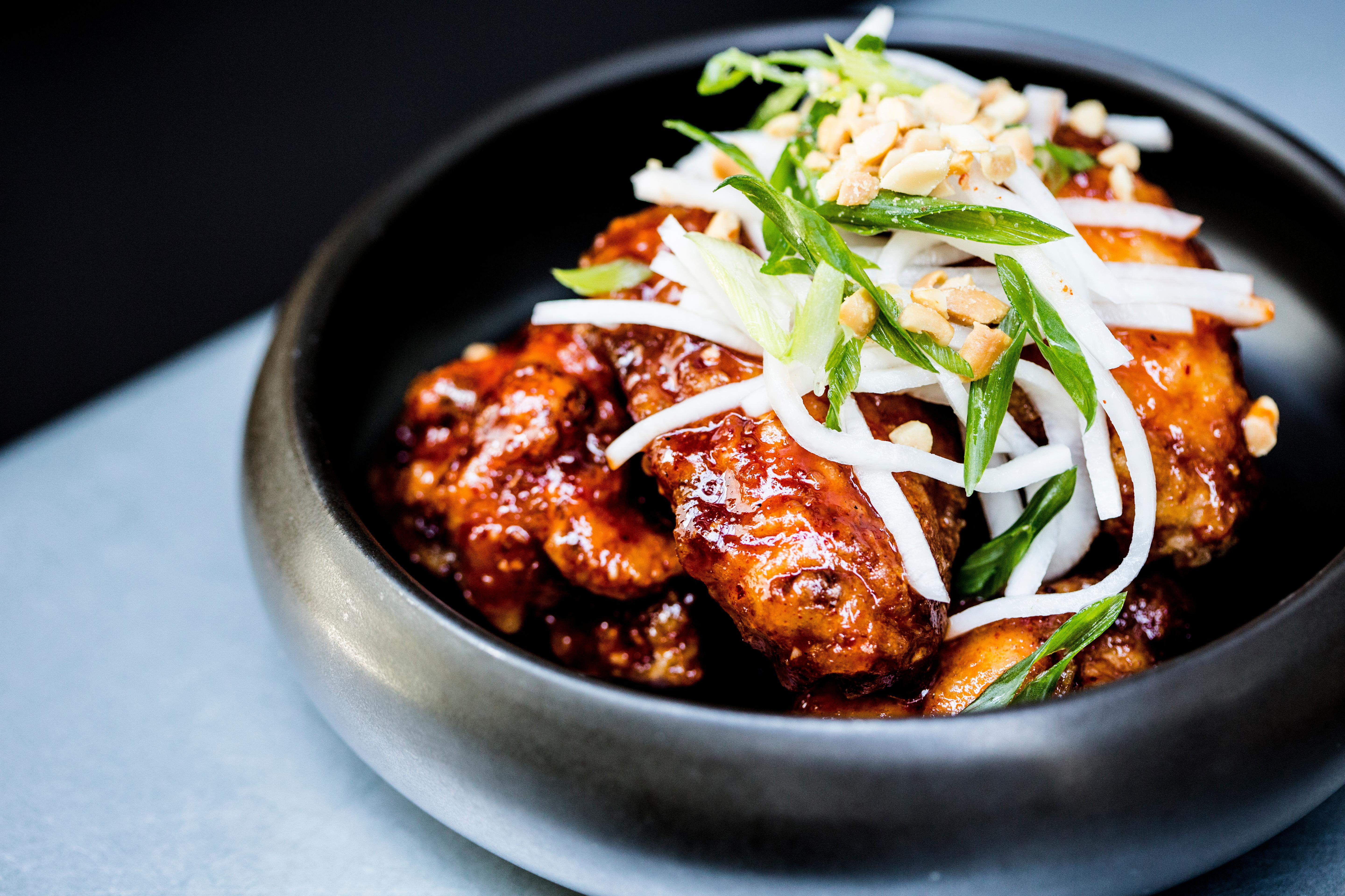 <p>Dirty Habit</p><p>At the hip spot at the Hotel Monaco, chef Kyoo Eom's fried chicken wings ($12) are available on both the dinner and late night menus. The signature shareable dish is inspired by Eom's Korean heritage, and comes with peanuts, chili threads and gochujang sauce. (Image: Dirty Habit)</p>