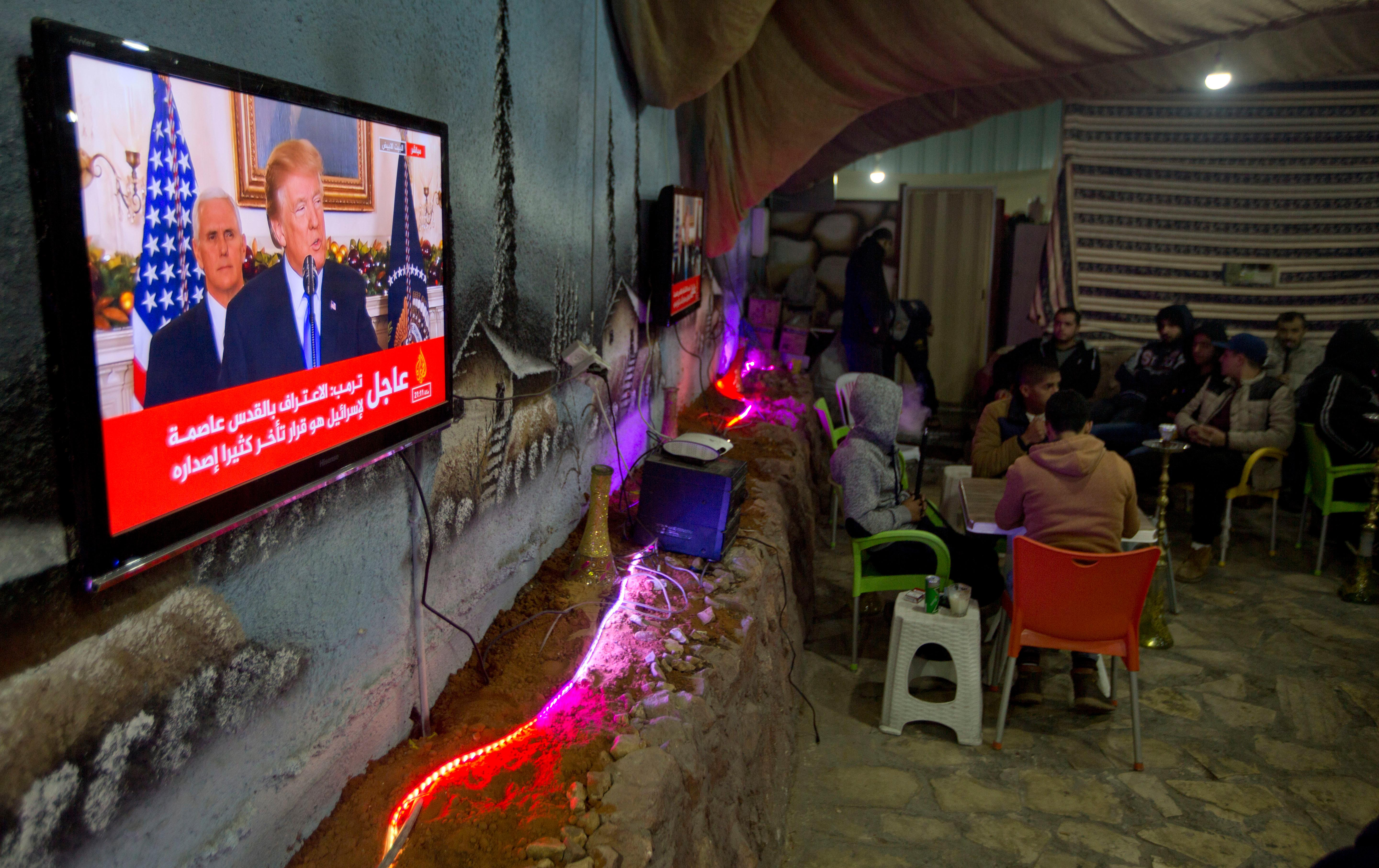 Palestinians play cards during U.S. President Donald Trump's televised speech in the West Bank City of Nablus, Wednesday, Dec. 6, 2017. Defying dire, worldwide warnings, President Donald Trump on Wednesday broke with decades of U.S. and international policy by recognizing Jerusalem as Israel's capital. (AP Photo/Majdi Mohammed)