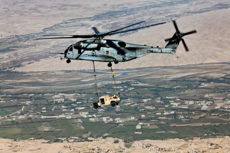 A CH-53E Super Stallion helicopter transports a high-mobility, multipurpose vehicle over Helmand province, Afghanistan. The Stallion is assigned to Marine Heavy Helicopter Squadron 462, which conducted the mission as part of demilitarization.