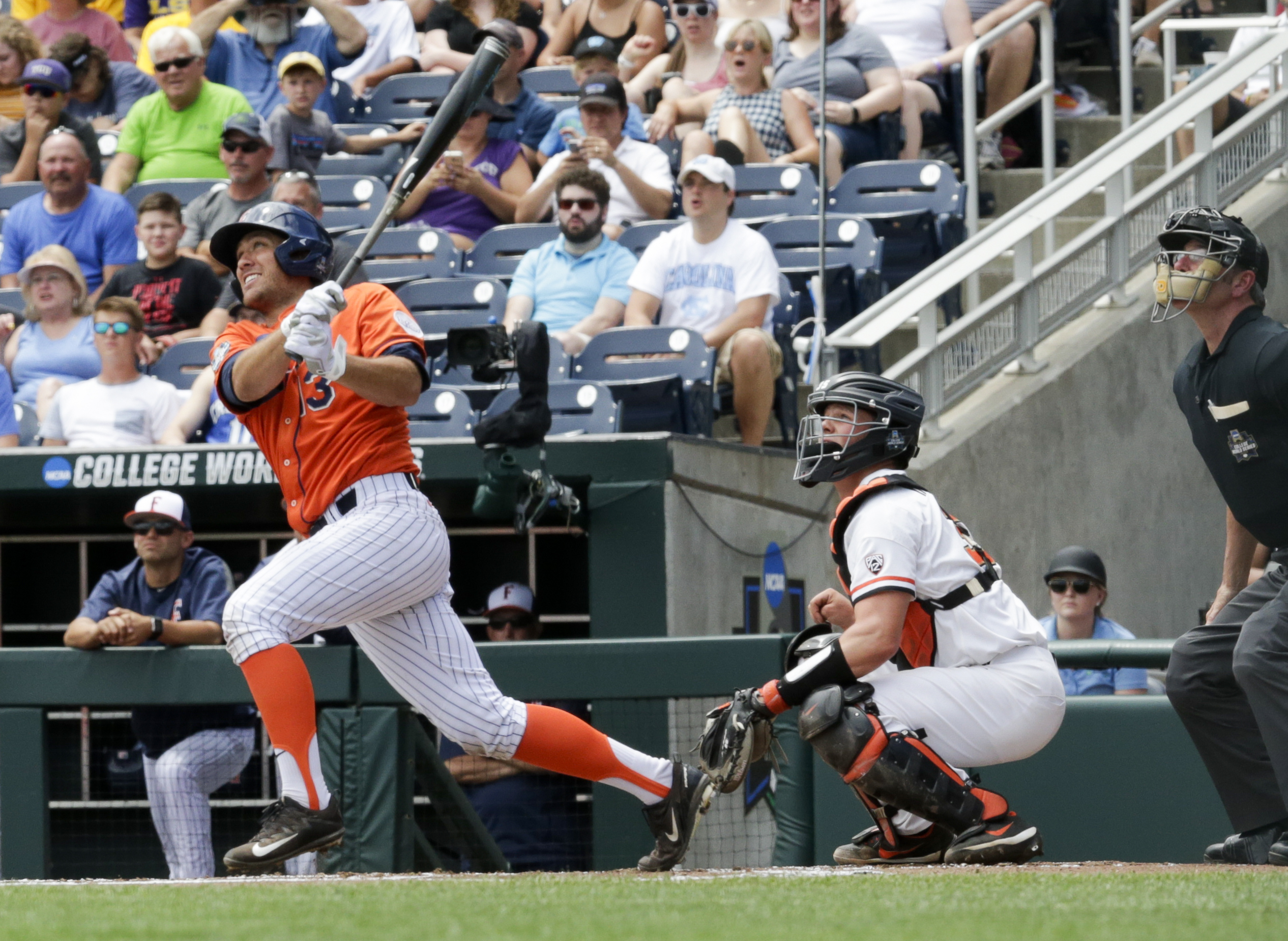 Cal State Fullerton's Timmy Richards (13) follows through on his three-run home run in the first inning of an NCAA mens College World Series baseball game against Cal State Fullerton in Omaha, Neb., Saturday, June 17, 2017. At right is Oregon State catcher Adley Rutschman. (AP Photo/Nati Harnik)