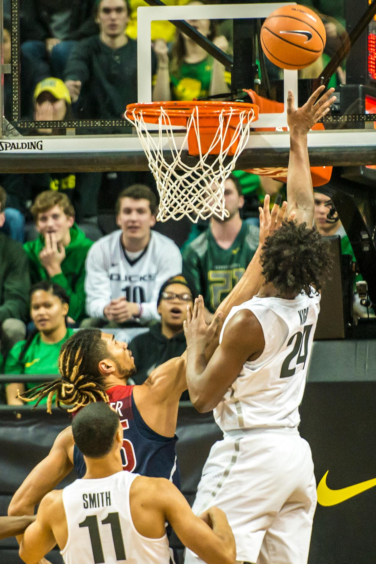 Oregon's Abu Kigab goes for a layup against Arizona defenders in their matchup at Matthew Knight Arena Saturday. The Ducks upset the fourteenth ranked Wildcats 98-93 in a stunning overtime win in front of a packed house of over 12,000 fans for their final home game to improve to a 19-10 (9-7 PAC-12) record on the season. Oregon will finish out regular season play on the road in Washington next week against Washington State on Thursday, then Washington on the following Saturday. (Photo by Colin Houck)