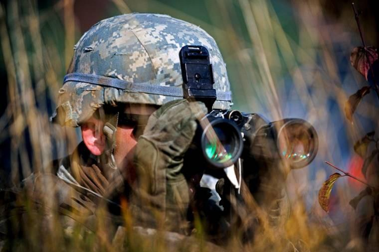 "A U.S. soldier uses binoculars to scan the terrain during reconnaissance training at the 7th Army Joint Multinational Training Command's Grafenwoehr Training Area, Germany, to prepare for upcoming exercise ""Steadfast Jazz"" in Poland."