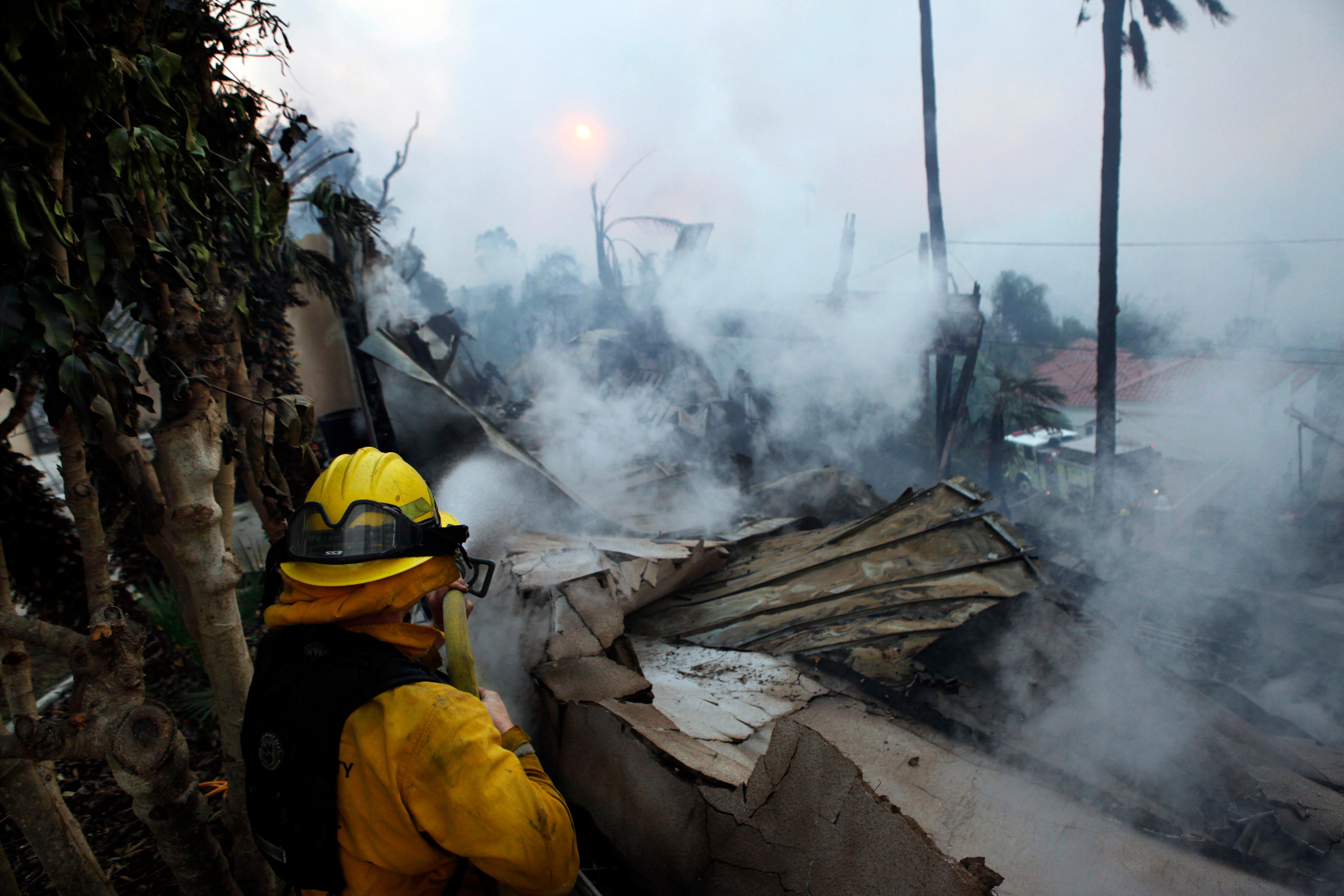 A firefighter hoses down smoldering debris in Ventura, Calif., Tuesday, Dec. 5, 2017. Ferocious Santa Ana winds raking Southern California whipped explosive wildfires Tuesday, prompting evacuation orders for thousands of homes. (Daniel Dreifuss via AP)