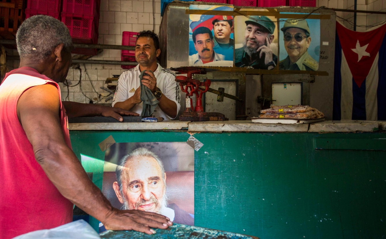 Posters with the portrait of Cuban Revolution leader Fidel Castro, Cuban President Raul Castro, Venezuelan President Nicolas Maduro and late Venezuelan President Hugo Chavez hang in a butcher shop in Havana, Cuba, Saturday, Aug. 13, 2016. As Castro celebrates his 90th birthday, the Cuban government has taken a low-key approach to Castro's birthday. There are no massive rallies or parades planned, no publicly announced visits from global dignitaries. (AP Photo/Desmond Boylan)