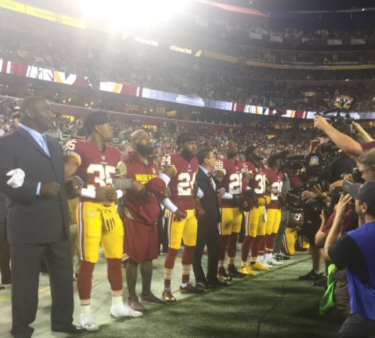 Some Washington Redskins players link arms with team owner Daniel Snyder during the National Anthem on Sunday, September 24, 2017, against the Oakland Raiders in Landover, Maryland. (Photo Courtesy of Kendall Griggs/ABC7)