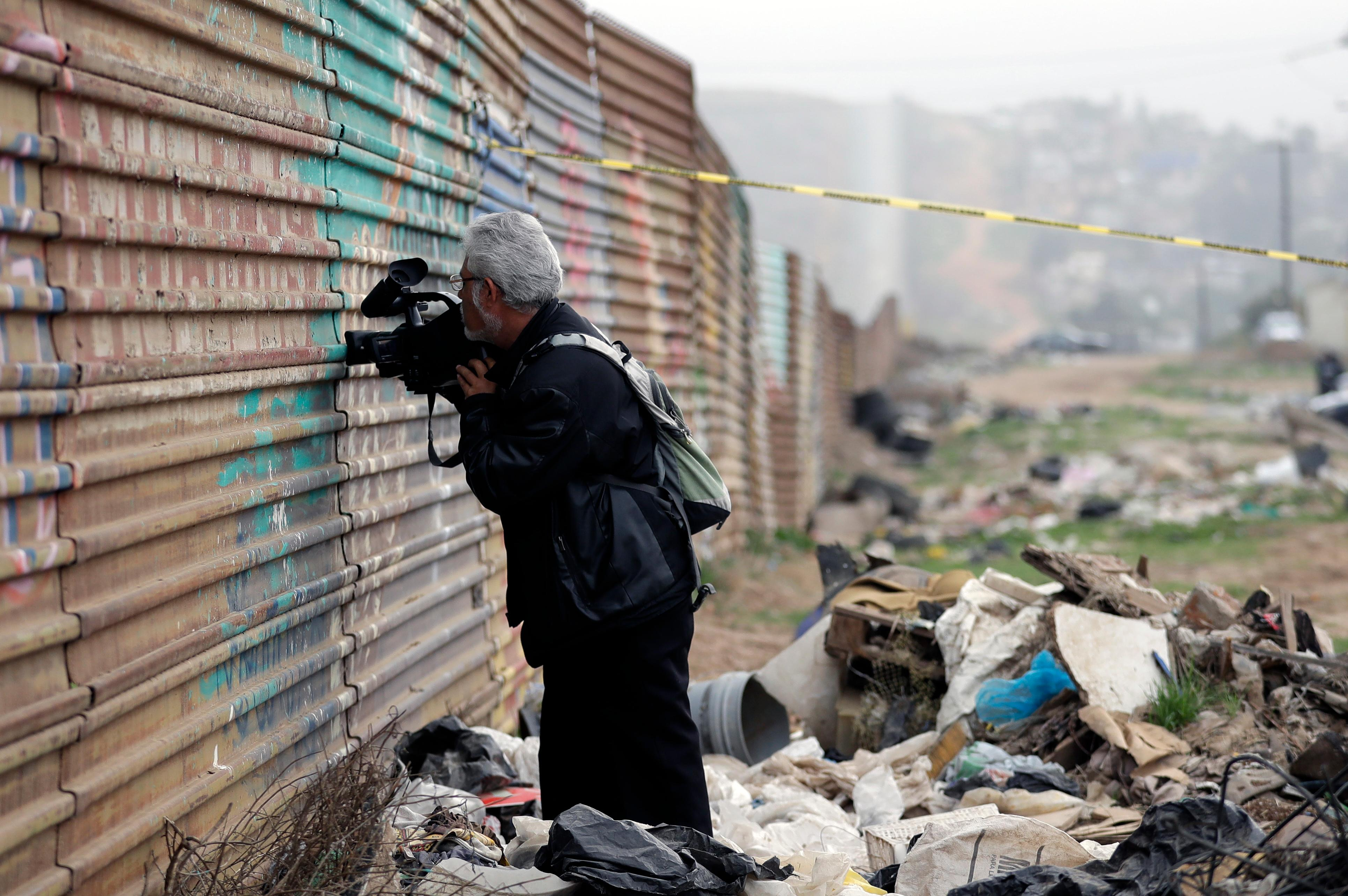 A journalist peers through a hole in the current border wall on the Mexico side of the border on Tuesday, March 13, 2018, in Tijuana, Mexico. President Trump is scheduled to visit the site of the border wall prototypes which are on the U.S. side of the wall. (AP Photo/Gregory Bull)