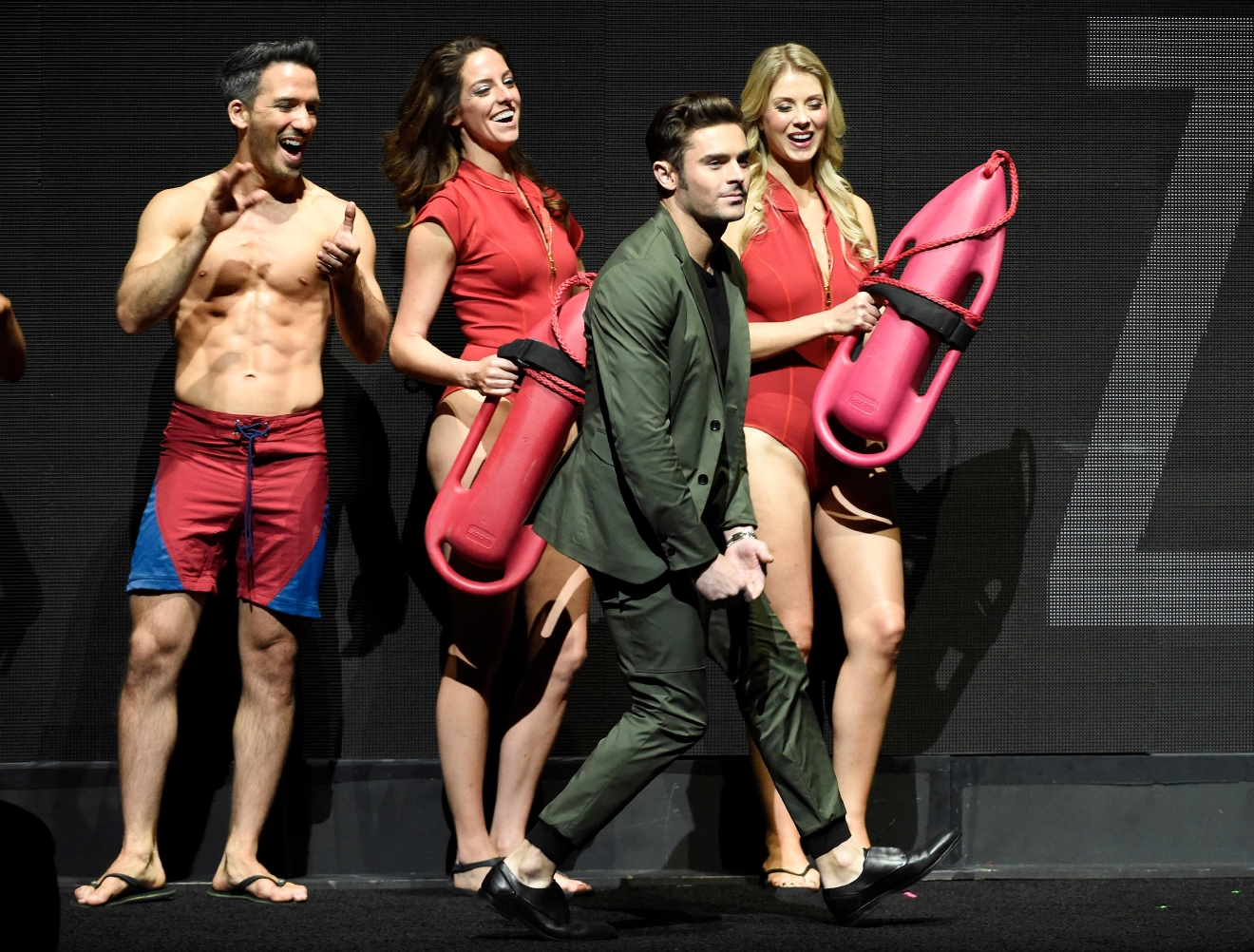 "Zac Efron, a cast member in ""Baywatch,"" walks past models dressed as lifeguards as he is introduced to the crowd during the Paramount Pictures presentation at CinemaCon 2017 at Caesars Palace on Tuesday, March 28, 2017, in Las Vegas. (Photo by Chris Pizzello/Invision/AP)"