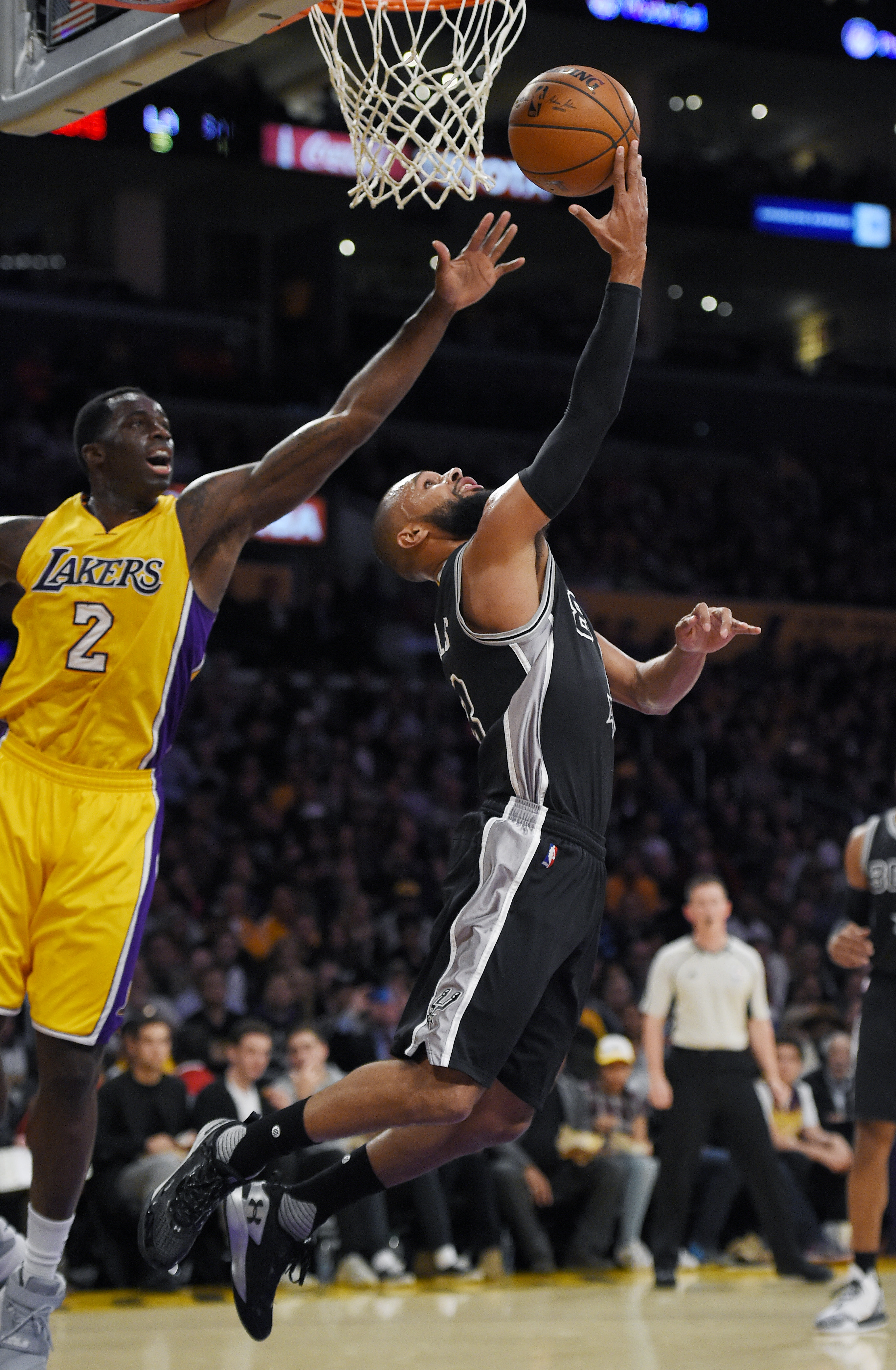 San Antonio Spurs guard Patty Mills, right, shoots as Los Angeles Lakers forward Brandon Bass defends during the first half of an NBA basketball game Friday, Jan. 22, 2016, in Los Angeles. (AP Photo/Mark J. Terrill)