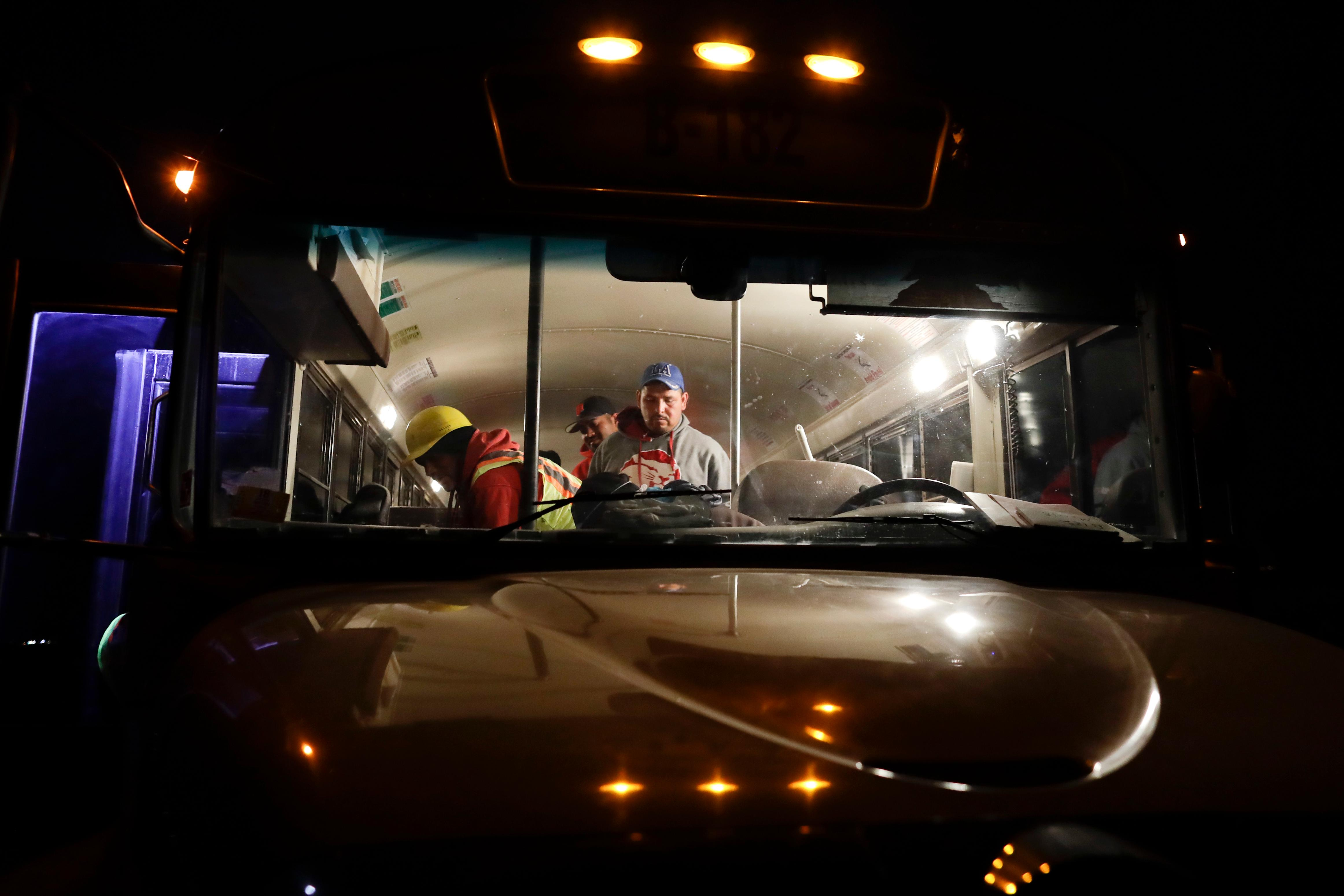 In this March 6, 2018 picture, farmworker Santiago Martinez, of Mexicali, Mexico, right, exits a bus as it arrives at a cabbage field ready for harvest, before dawn outside of Calexico, Calif. As Trump visits the border for the first time as president on Tuesday, the harvest is a reminder of how little has changed despite heated rhetoric in Washington. (AP Photo/Gregory Bull)