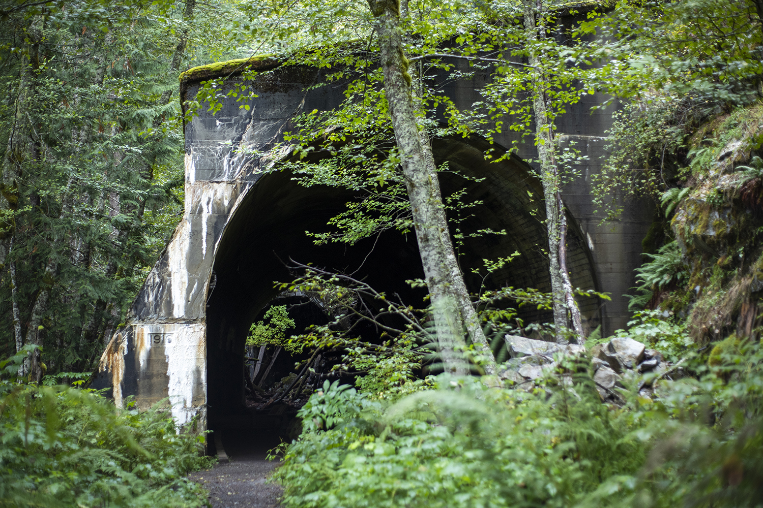 Dates stamped on the outside of several tunnels along the path tell the tale of a once-busy railway now defunct from the catastrophic natural disaster decades prior. (Image: Rachael Jones / Seattle Refined)