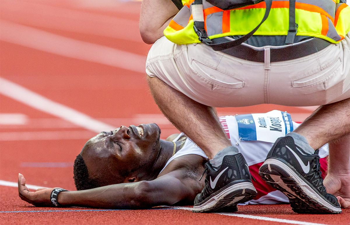 Alabama's Antibahs Kosgei is check on by a medic after collapsing at the finish of the 10,000 meter run. Photo by August Frank, Oregon News Lab