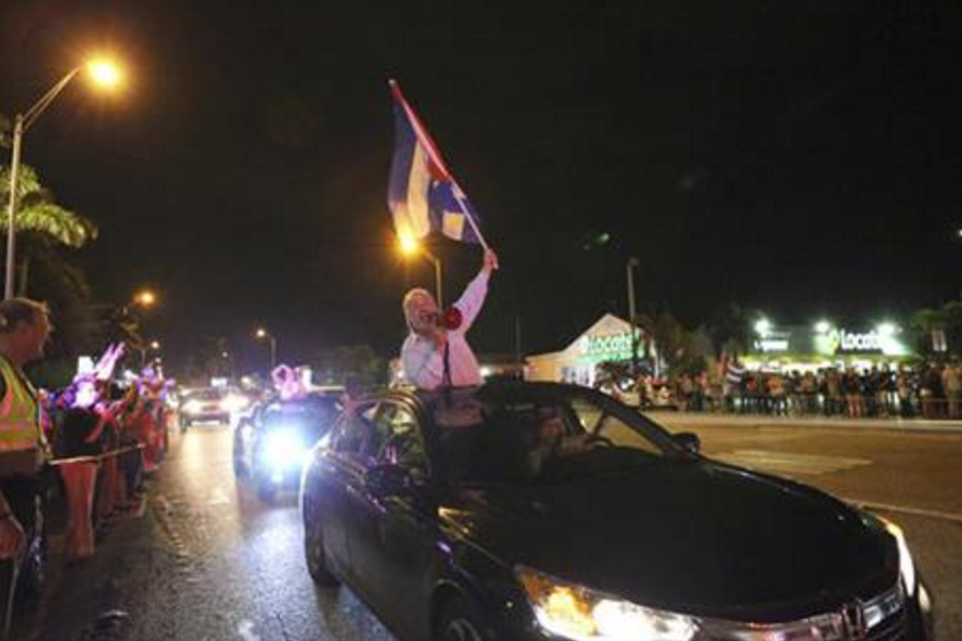The Cuban community celebrates the announcement that Fidel Castro died as they drive by in cars and line the street in front of La Carreta Restaurant, early Saturday, Nov. 26, 2016, in Miami. Within half an hour of the Cuban government's official announcement that former President Fidel Castro had died, Friday, Nov. 25, 2016, at age 90, Miami's Little Havana teemed with life - and cheers. (David Santiago/El Nuevo Herald via AP)