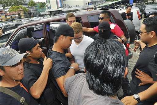 Lindsey Petersen, center, is escorted by police as he arrives at court in Kota Kinabalu, in eastern Sabah state on Borneo island, Malaysia.