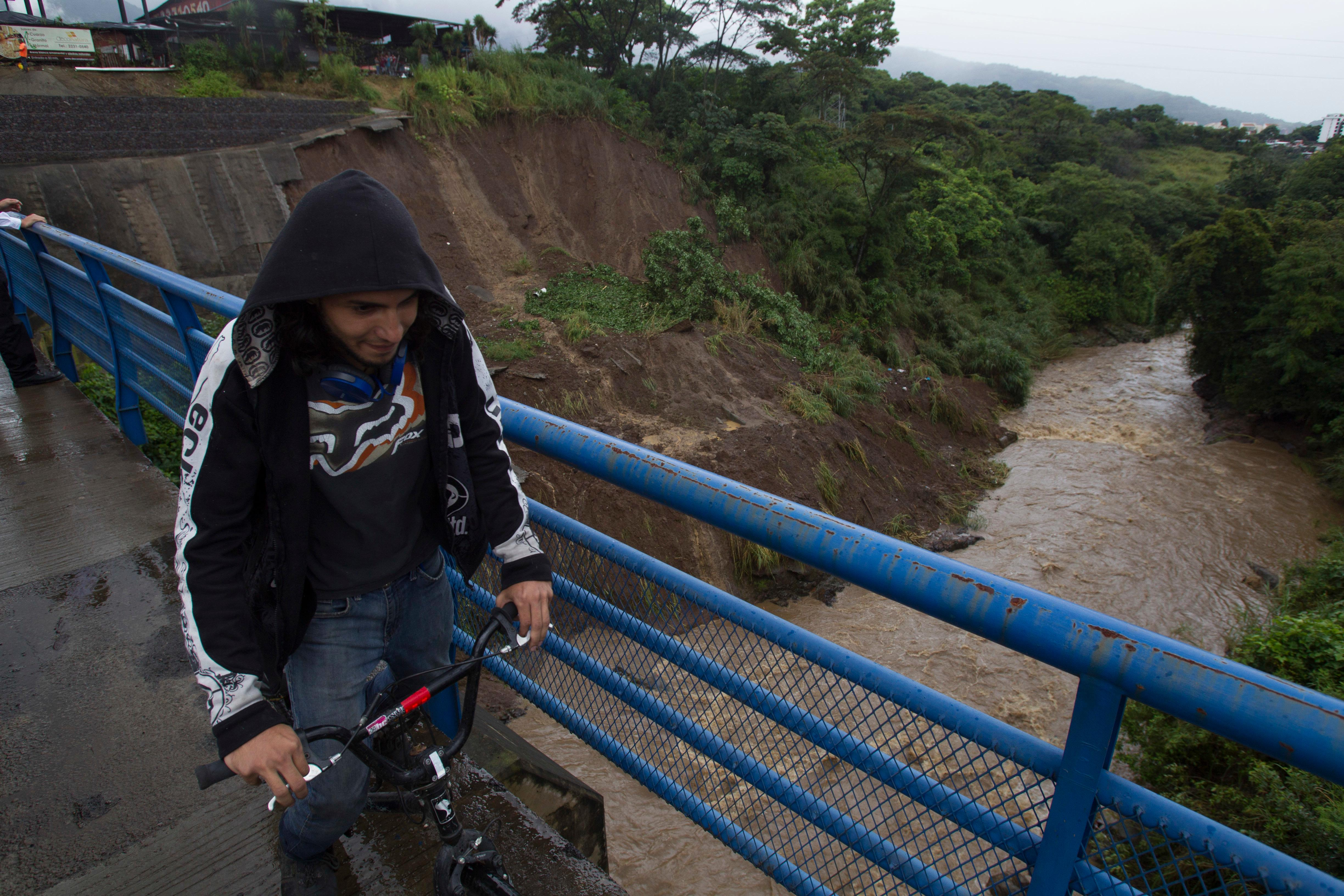 A cyclist rides over a bridge over the Maria Aguilar river on the outskirt San Jose, Costa Rica, Thursday, Oct. 5, 2017. Tropical Storm Nate formed off the coast of Nicaragua on Thursday and was being blamed for at least 17 deaths in Central America as it spun north toward a potential landfall on the U.S. Gulf Coast as a hurricane over the weekend. (AP Photo/Moises Castillo)