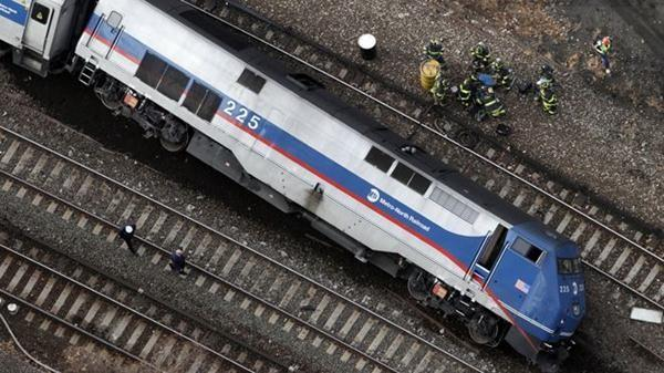 The locomotive of the train is seen resting on its side after the train derailed.