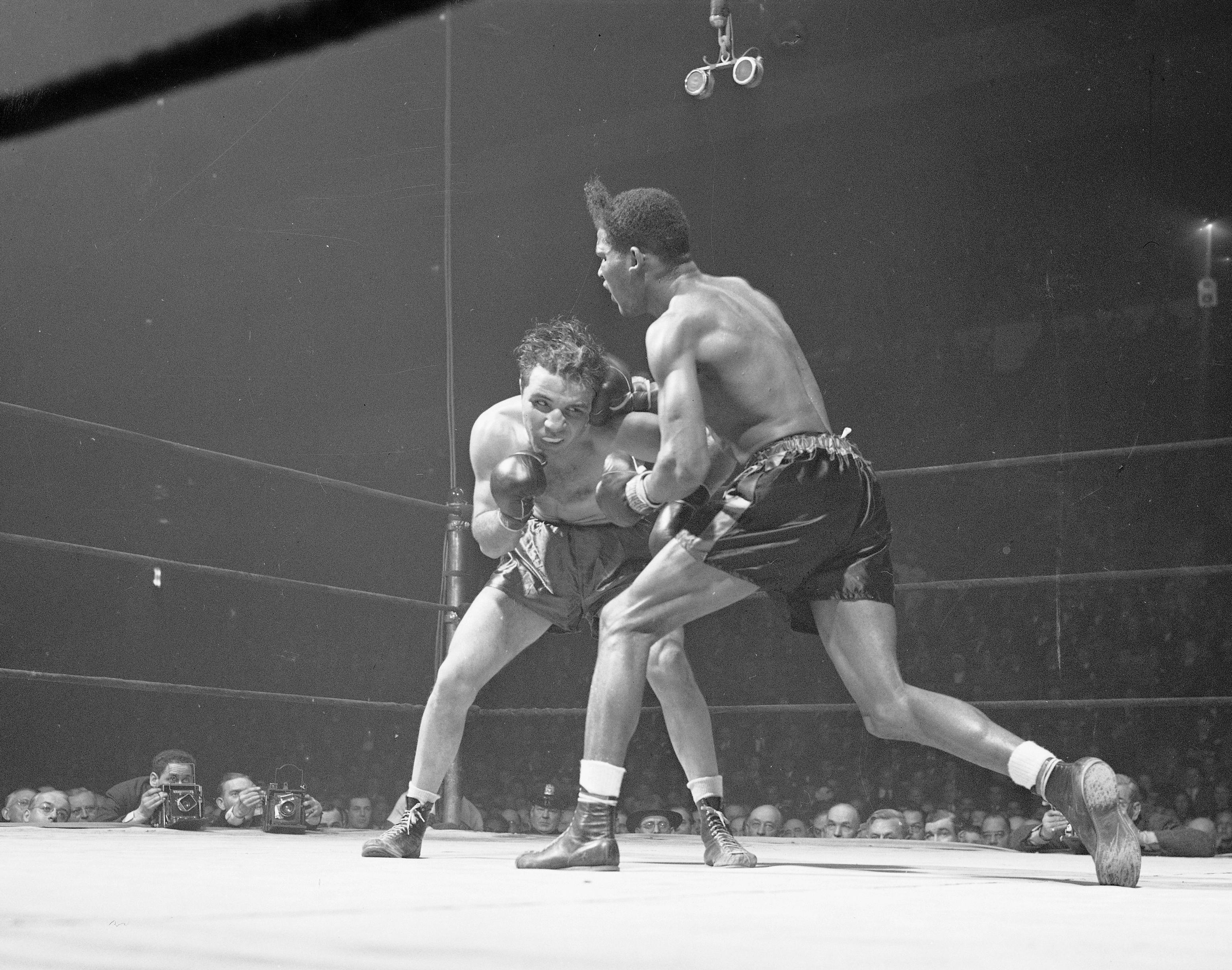 "FILE - In this Feb. 23, 1945, file photo, Jake LaMotta, left, of the Bronx borough of New York, and Ray Robinson of the Harlem section of New York, fight at Madison Square Garden in New York. Robinson won the fight on a decision. LaMotta fought Sugar Ray Robinson six times, handing Robinson his first defeat. LaMotta, whose life was depicted in the film ""Raging Bull,"" died Tuesday, Sept. 19, 2017, at a Miami-area hospital from complications of pneumonia. He was 95. (AP Photo/Matty Zimmerman, File)"