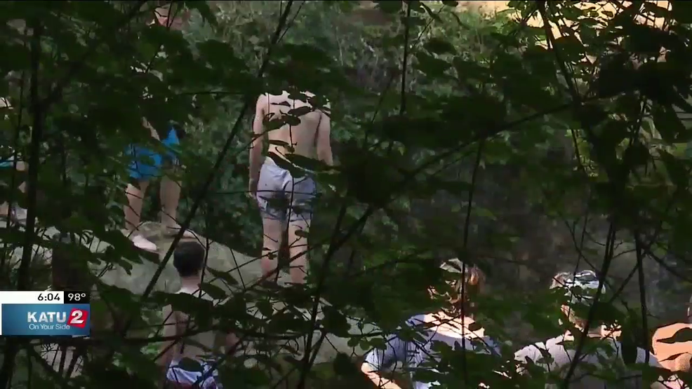 Rescue crews work to free swimmers trapped under falls ...