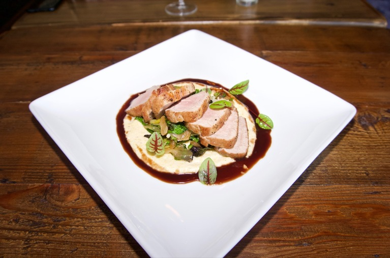 Pork tenderloin with creamy polenta, wilted greens, caramelized onions, and a currant demi-glace / Image: Brian Planalp // Published: 5.14.18