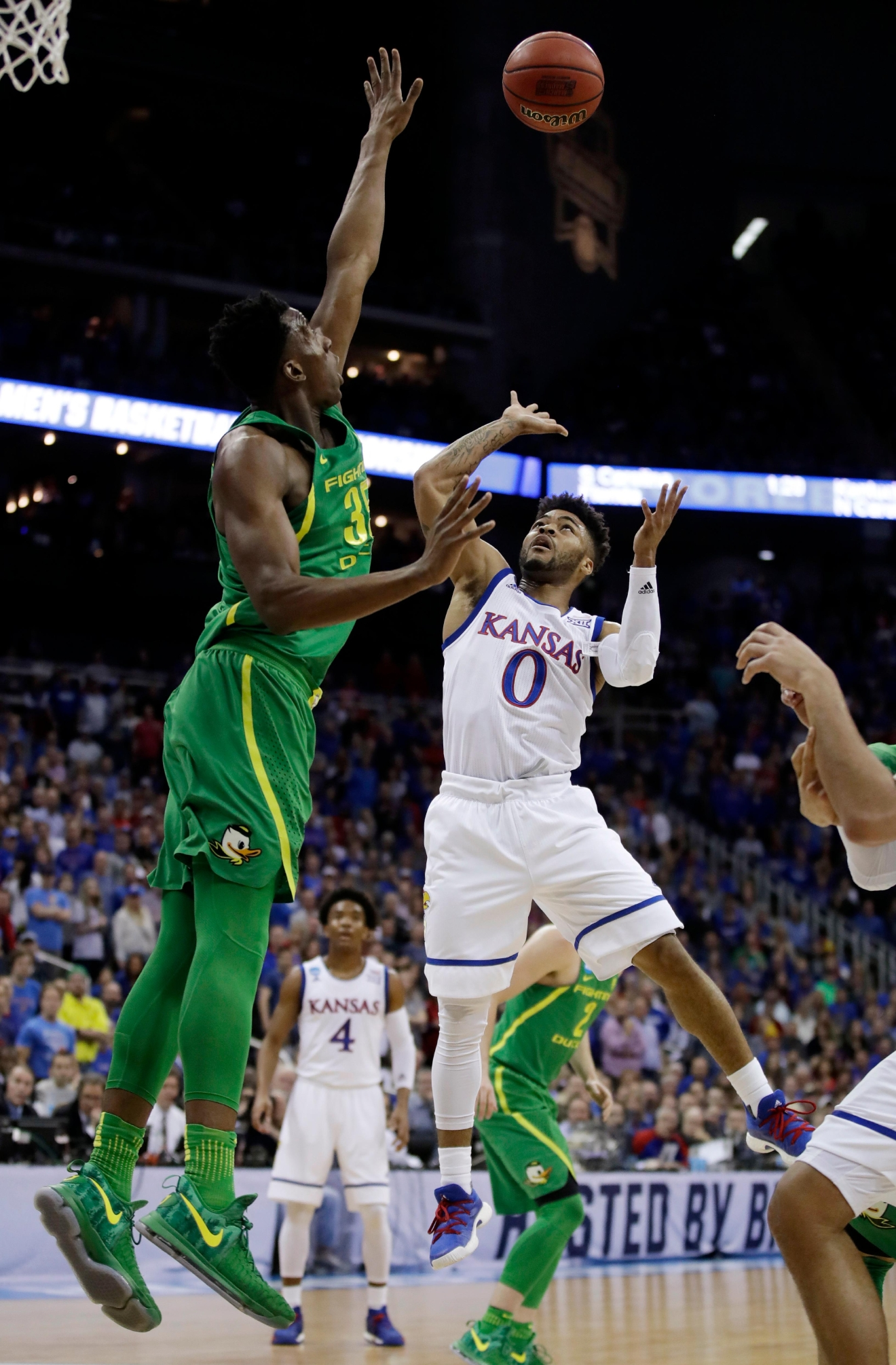Kansas guard Frank Mason III (0) shoots over Oregon forward Kavell Bigby-Williams, left, during the first half of the Midwest Regional final of the NCAA men's college basketball tournament, Saturday, March 25, 2017, in Kansas City, Mo. (AP Photo/Charlie Riedel)