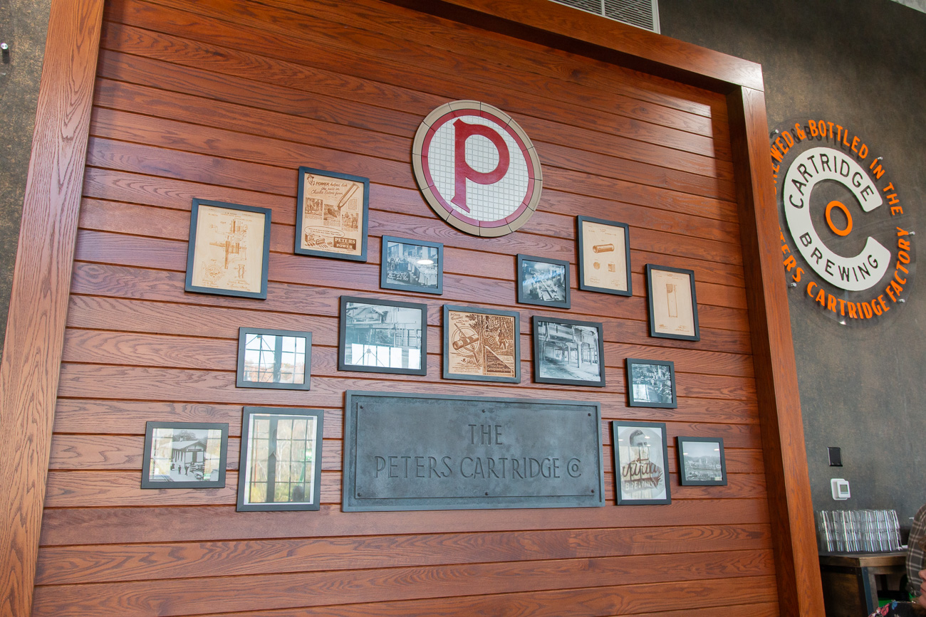 "Lindsey personally handled the interior details that honor the site's past. This includes special touches such as the tap handles being giant shells with the Cartridge ""C"" on top, the handmade flight boards made to represent the ammo boxes of Peters Cartridge, the custom river tables throughout the brewery, as well as the ""honoring the past wall"" in the dining room that was a way to continue to share the story of the local landmark. ""I think noticing those details will be fun for people when they come in here [to see] that we did not skimp on that and we did not do anything I think generic. The devil is in the details and we hit those out of the park,"" Lindsey says. / Image: Elizabeth A. Lowry // Published: 11.25.20"