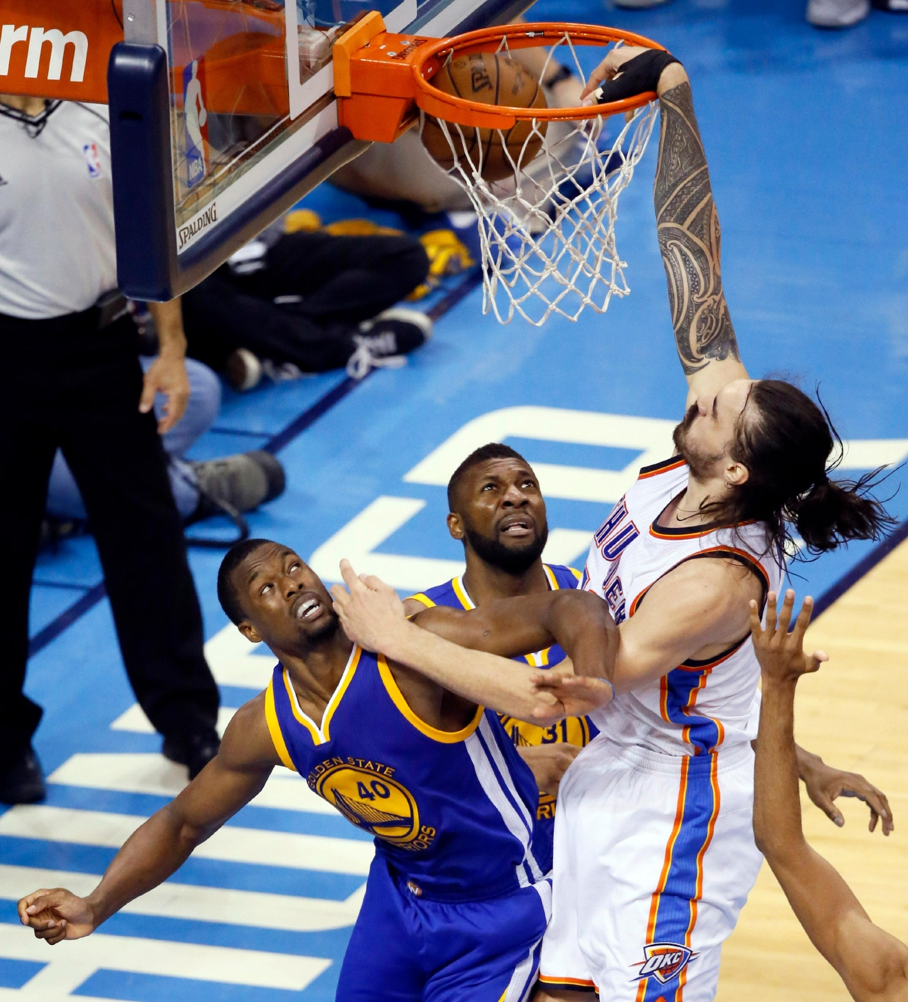 Oklahoma City Thunder center Steven Adams (12) dunks over Golden State Warriors forward Harrison Barnes (40) and center Festus Ezeli (31) during the second half in Game 4 of the NBA basketball Western Conference finals in Oklahoma City, Tuesday, May 24, 2016. (AP Photo/Sue Ogrocki)
