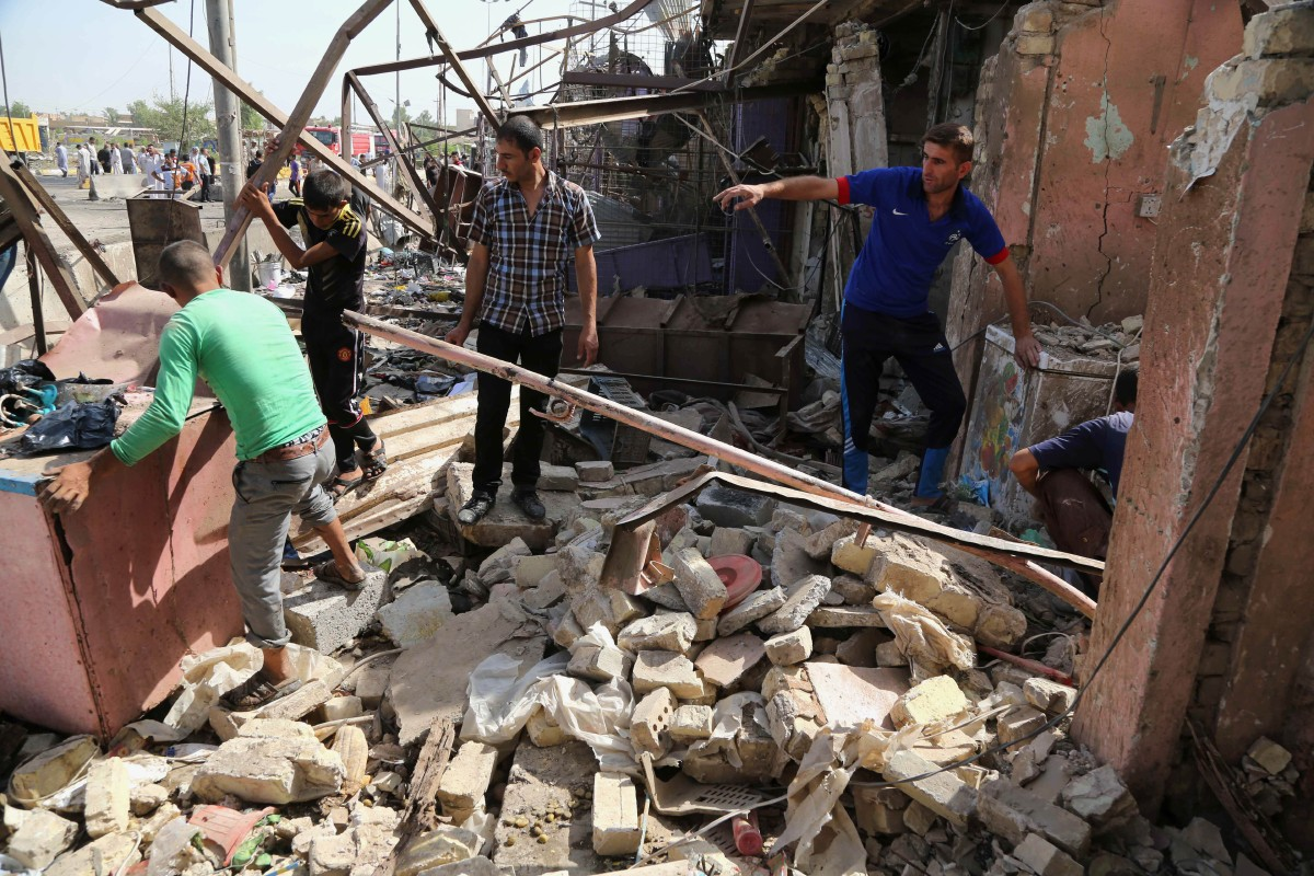 Civilians clean up at the scene of a suicide car bombing at a busy market in Khan Bani Saad in the Diyala province, about 20 miles (30 kilometers) northeast of Baghdad, Iraq, Saturday, July 18, 2015. A suicide car bombing in Iraq's eastern Diyala province killed at least 80 people gathered at a marketplace to mark the end of the holy month of Ramadan on Friday. (AP Photo/Karim Kadim)