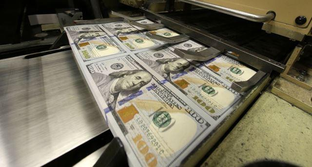 Uncut $100 bills run through cutting machine at the Bureau of Engraving and Printing Western Currency Facility in Fort Worth, Texas.