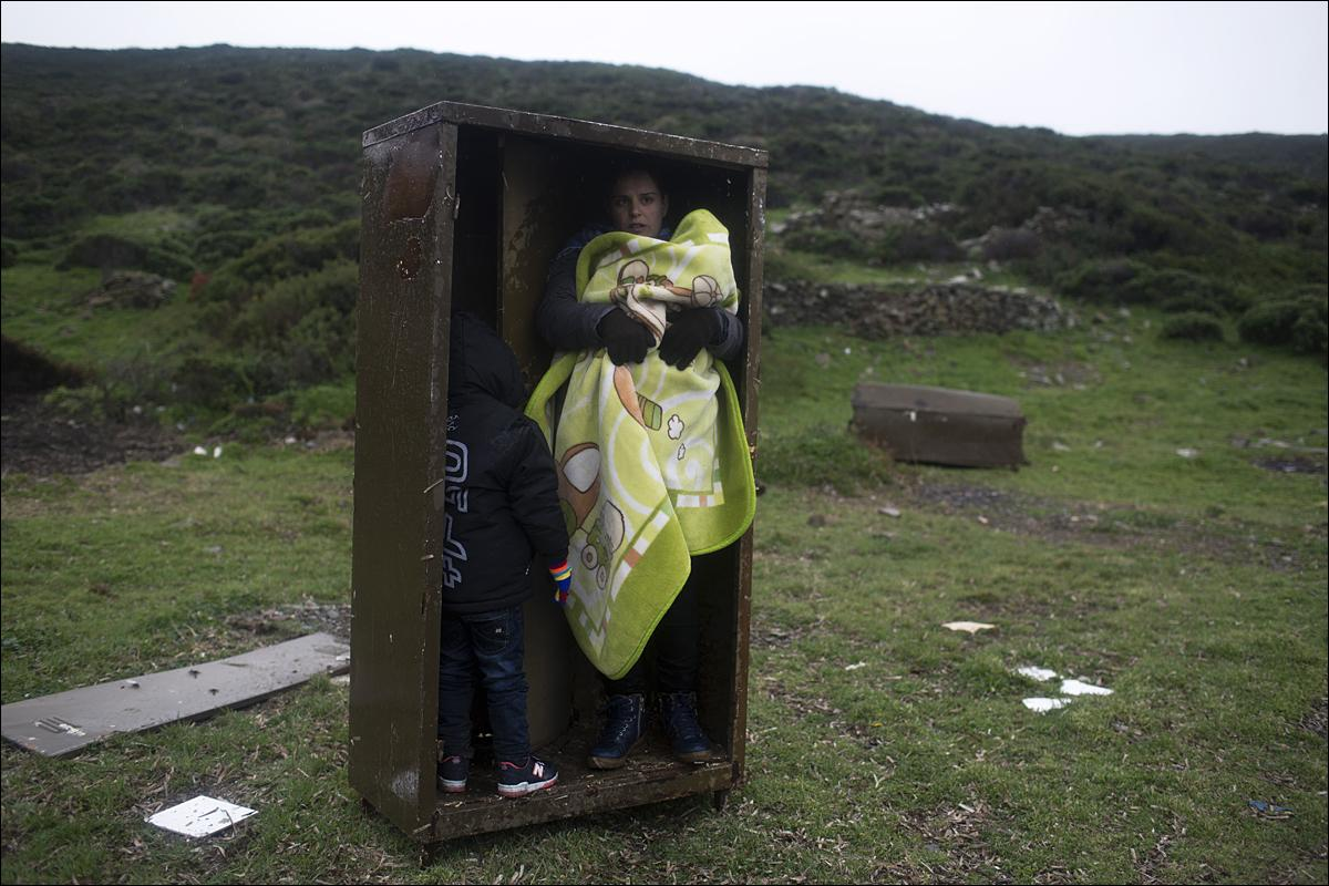 A Syrian woman with her children takes a shelter in a iron box during a rainfall, after they arrived from Turkey to the Greek deserted island of Pasas near Chios on Wednesday, Jan. 20, 2016 . Thousand of migrants and refugees continue to reach Greece's shores despite the winter weather. (AP Photo/Petros Giannakouris)