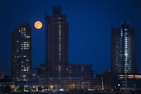 A perigee moon, also known as a supermoon, rises over the Queens borough of New York, Saturday, July 12, 2014.
