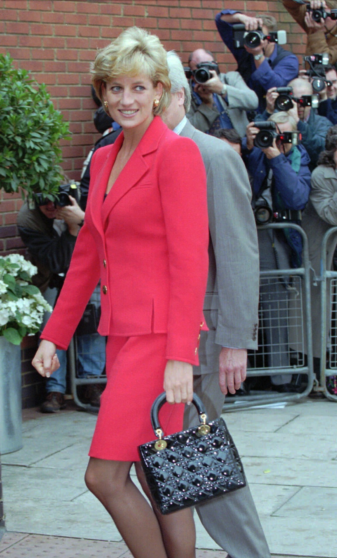 "FILE - In this Oct. 8, 1996 file photo, Diana, Princess of Wales walks past the press in London. This outfit is featured in an exhibition of 25 dresses and outfits worn by Diana entitled ""Diana: Her Fashion Story"" at Kensington Palace in London, opening on Friday, Feb. 24, 2017. (AP Photo/Adrian Dennis, file)"