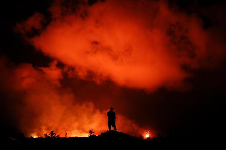 FILE  - In this May 18, 2018 file photo, Peter Vance, 24, photographs lava erupting in the Leilani Estates subdivision near Pahoa, Hawaii. While Hawaii Island features two massive volcanoes, with the highest, Mauna Kea, reaching nearly 14,000 feet (4,265 meters) above sea level and sometimes capped with snow, Kilauea is far less prominent. But because it's been active since 1983, the volcano's fiery flow of lava into the sea has been a popular cruise destination for photographers and tourists. (AP Photo/Jae C. Hong, File)
