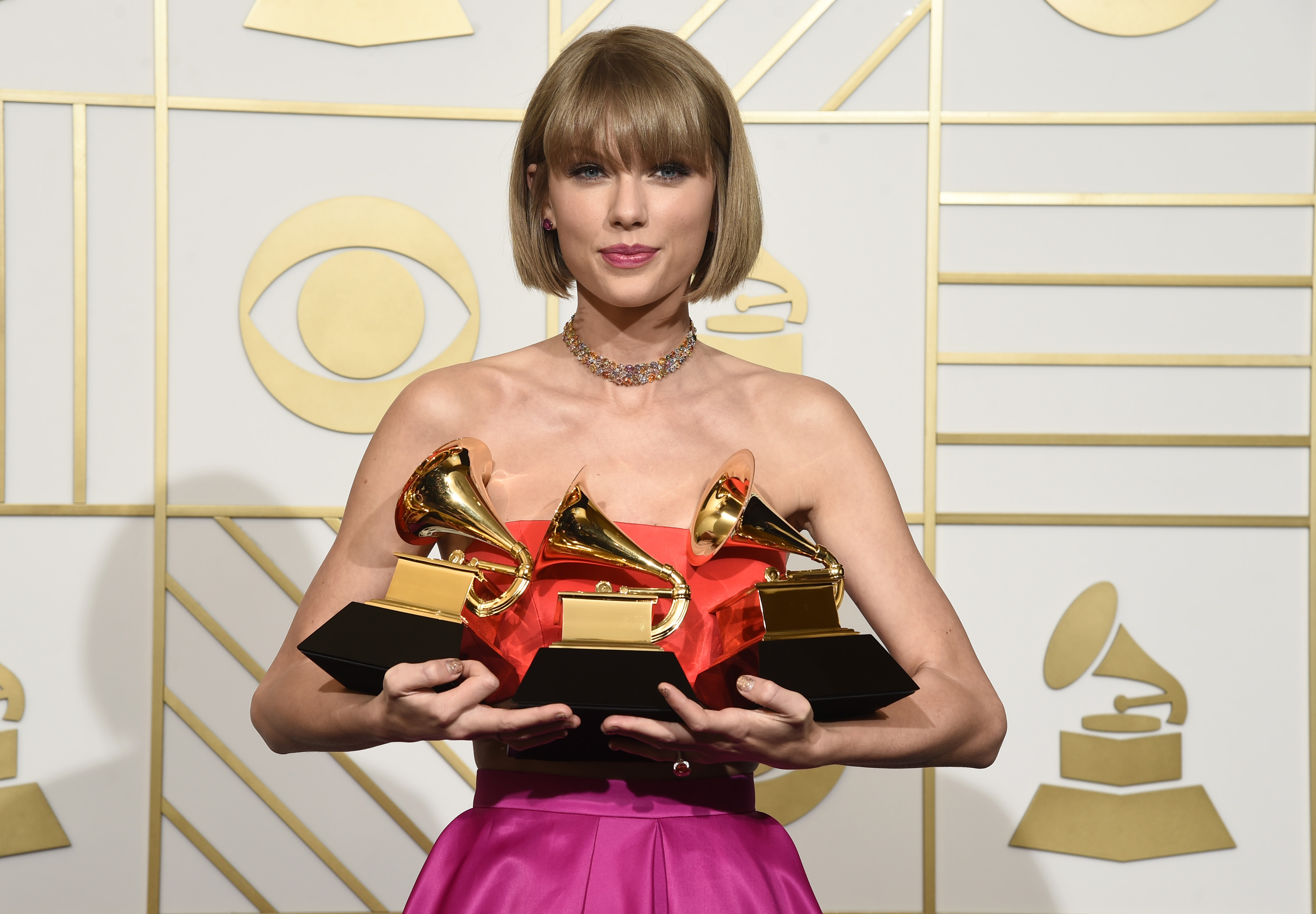 "Taylor Swift poses in the press room with the awards for album of the year for 1989, pop vocal album for 1989 and best music video for ""Bad Blood"" at the 58th annual Grammy Awards at the Staples Center on Monday, Feb. 15, 2016, in Los Angeles. (Photo by Chris Pizzello/Invision/AP)"