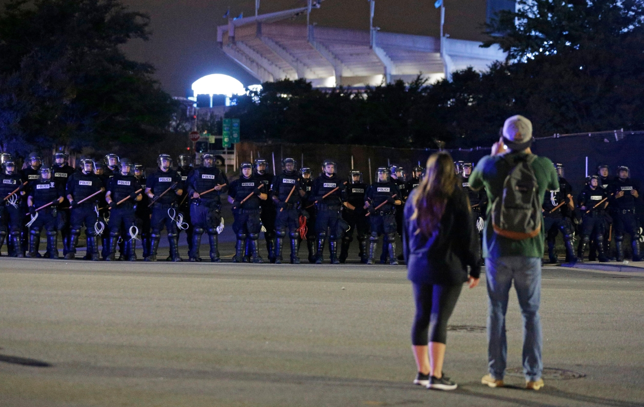 A couple looks at line of police officers blocking the access road to I-277 on the third night of protests in Charlotte, N.C. Thursday, Sept. 22, 2016, following Tuesday's fatal police shooting of Keith Lamont Scott in Charlotte, N.C. (AP Photo/Chuck Burton)