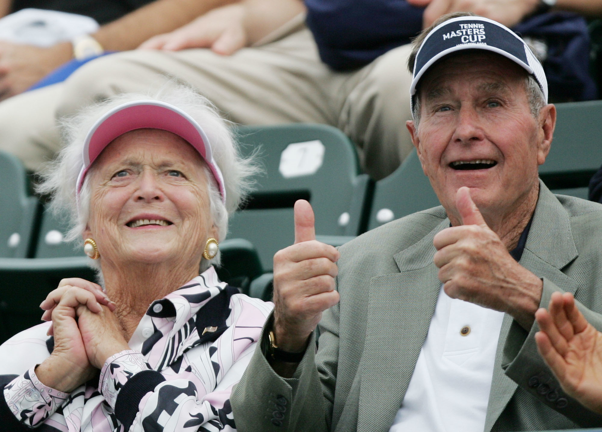 "FILE - In this Nov. 16, 2004 file photo, former President George Bush, right, gives a thumbs-up while he and his wife, Barbara, left, attend the Tennis Masters Cup tournament in Houston. With her husband still at her side, Barbara Bush has decided to decline further medical treatment for health problems and focus instead on ""comfort care"" at their home in Houston. Family spokesman Jim McGrath disclosed Barbara Bush's decision Sunday, April 15, 2018. (AP Photo/David J. Phillip, File)"