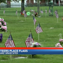 Volunteers place flags for fellow veterans at Calvary Cemetery