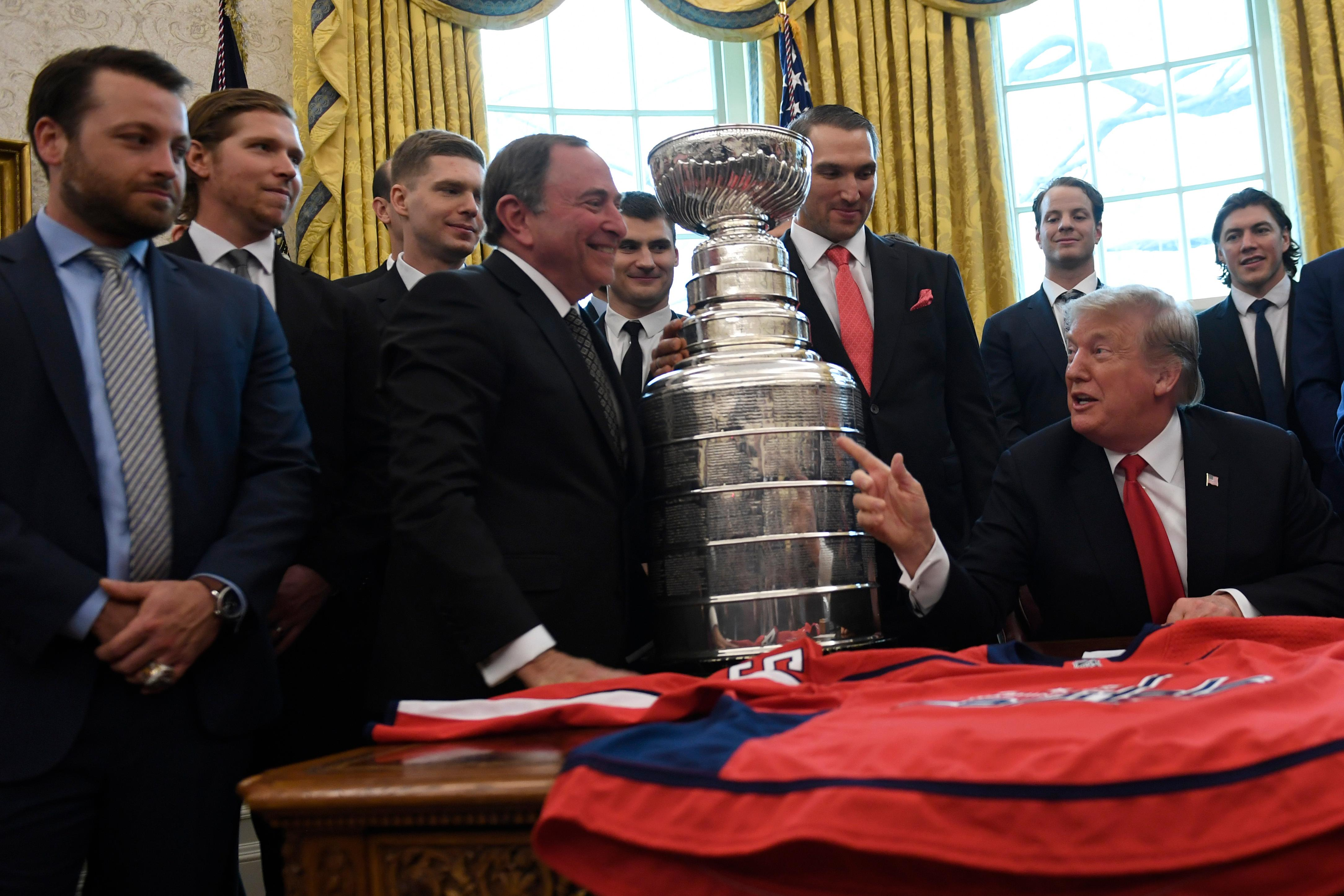 President Donald Trump, second from right, points to NHL Commissioner Gary Bettman, fourth from left, as they are surrounded by members of the 2018 Stanley Cup Champion Washington Capitals hockey team in the Oval Office of the White House in Washington, Monday, March 25, 2019. (AP Photo/Susan Walsh)