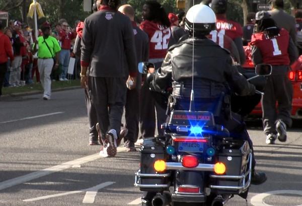 A Tuscaloosa Police Department officer escorts Alabama players on a motorcycle during the BCS Championship parade on Saturday, January 19, 2013.
