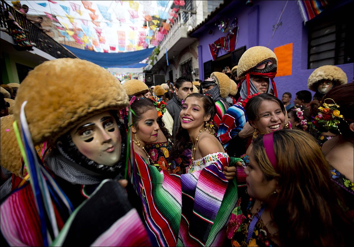 "Traditional ""Parachicos"" dancers wearing wooden masks perform on the street during a Catholic celebration in Chiapas De Corzo, Mexico, Wednesday, Jan. 20, 2016. The festivity, which has been included in UNESCO's Intangible Cultural Heritage Lists, takes place from Jan. 4 to 23 every year in honor of the Christ of Esquipulas, Saint Anthony Abbot and Martyr Saint Sebastian. (AP Photo/Eduardo Verdugo)"